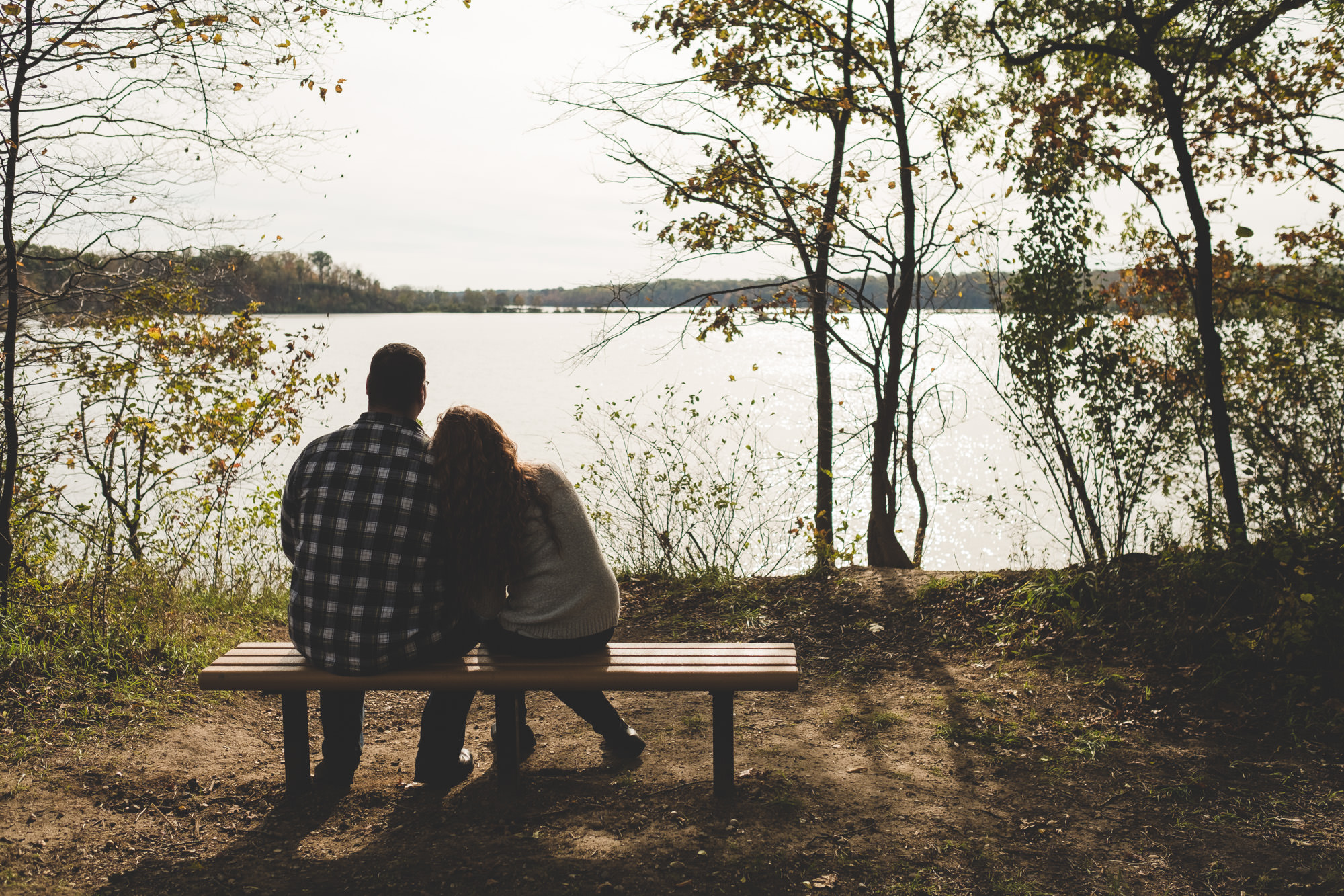 couple-sitting-on-eagle-creek-state-park-bench-looking-out-at-lake