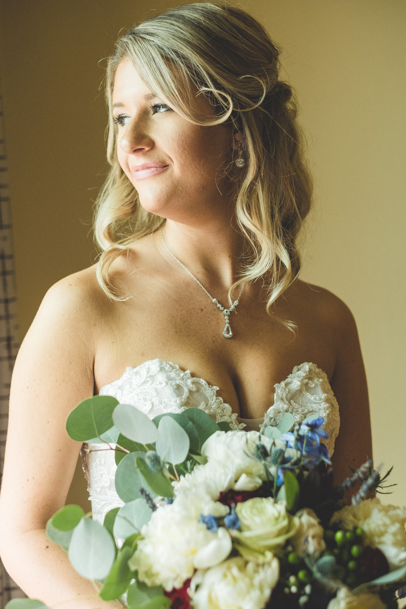 Bride-looking-out-window-holding-flowers