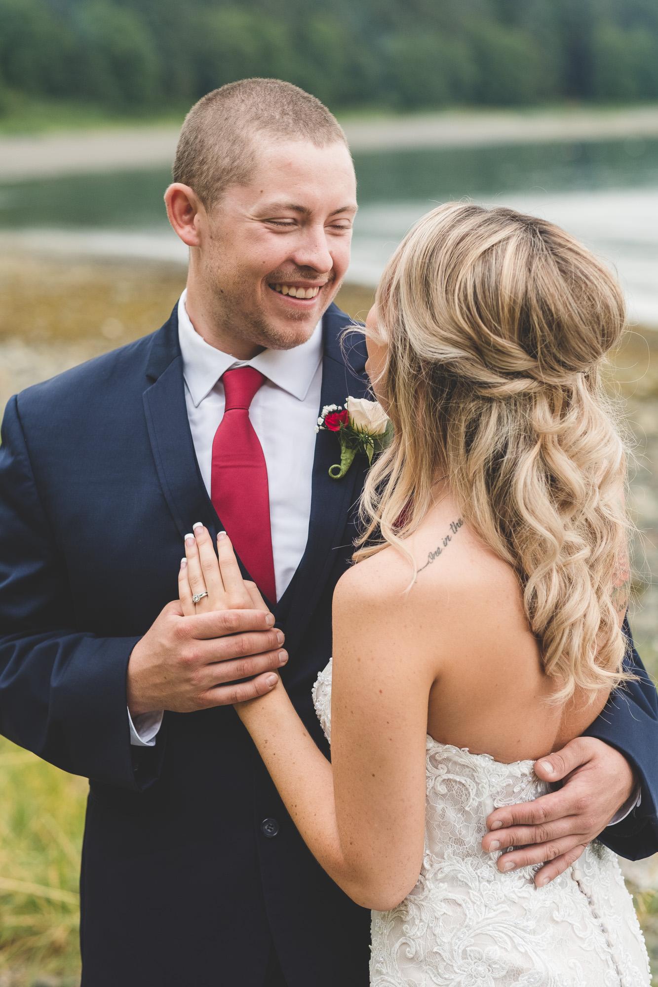 groom-in-blue-suit-red-tie-smiling-at-bride