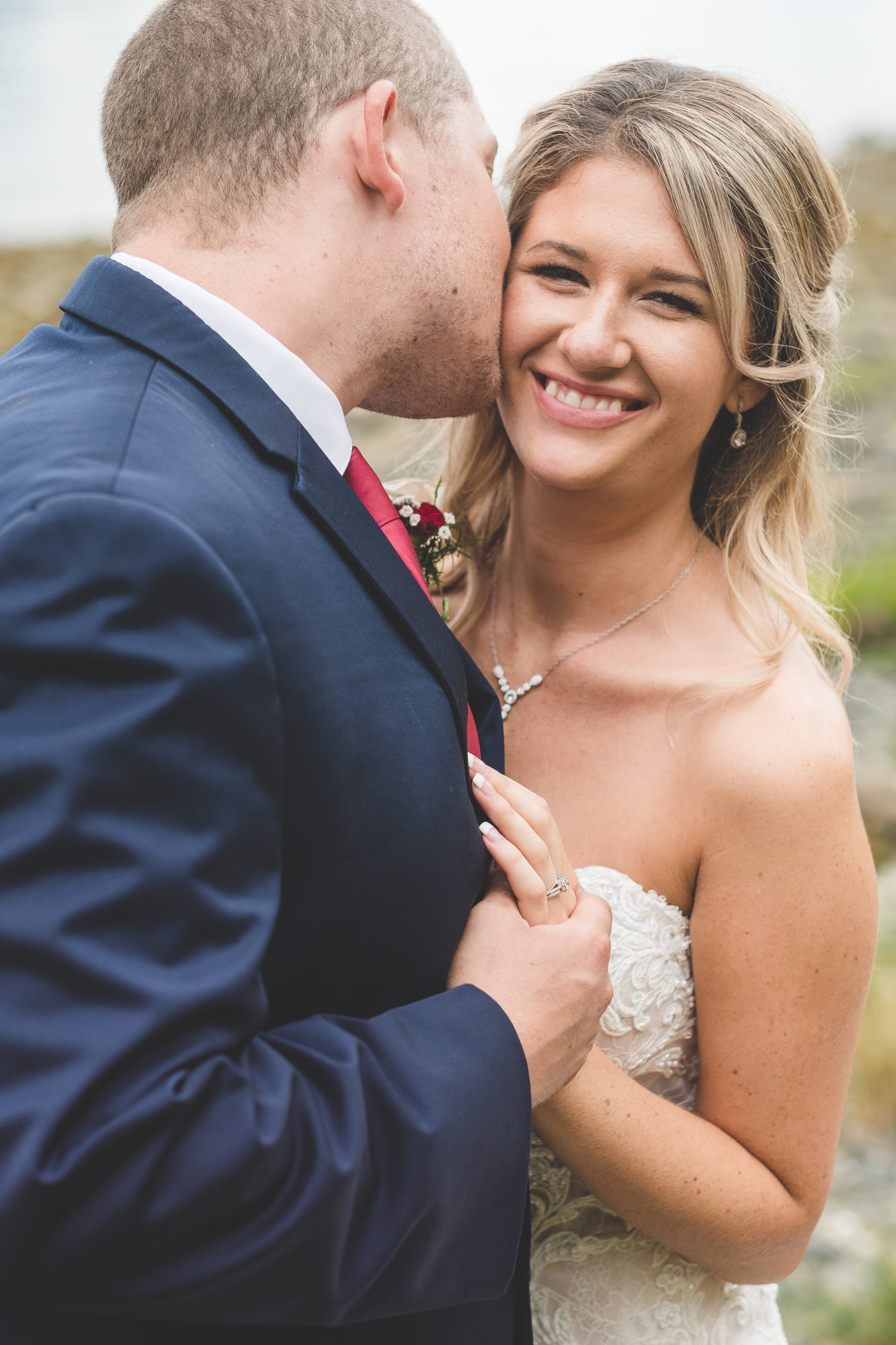 bride-smiling-while-groom-kisses-cheek