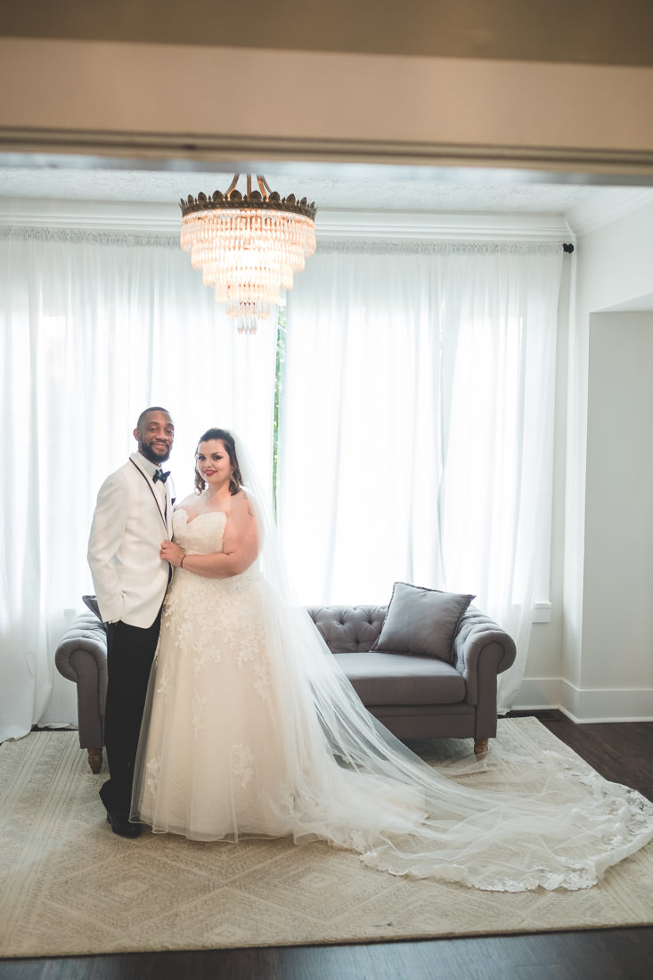 Wedding-couple-in-white-tux-under-chandelier
