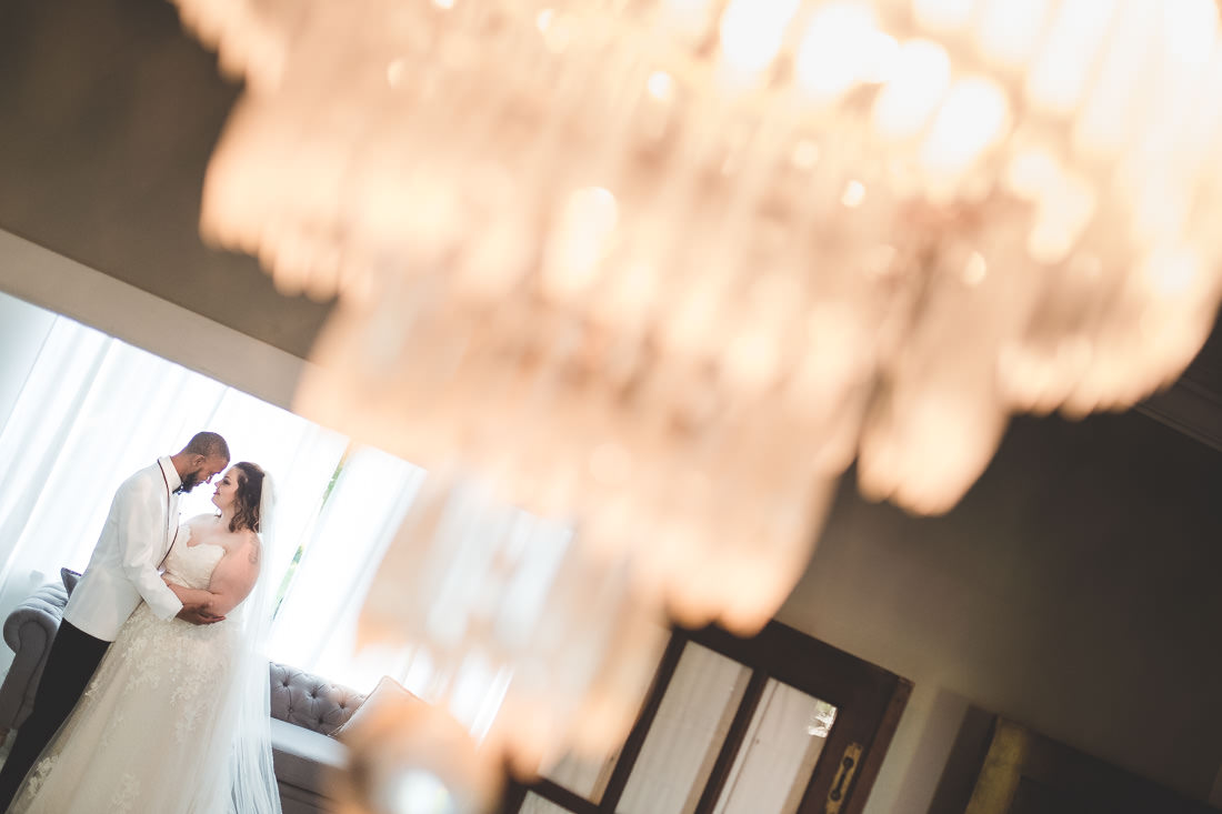 bride-groom-in-front-of-window-through-chandelier