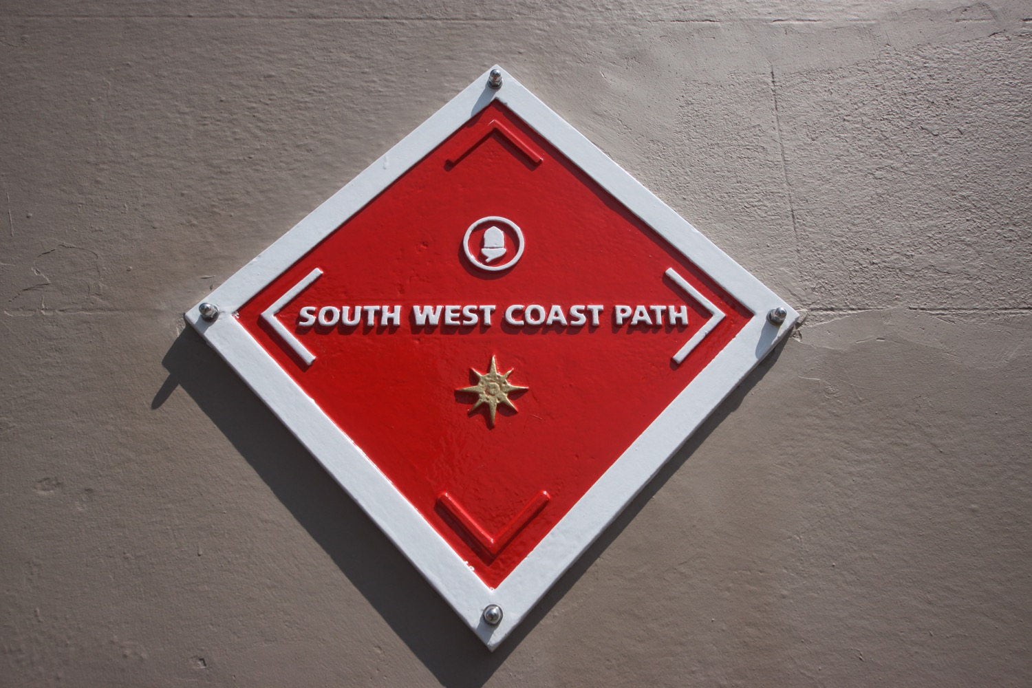 red south west coast path marker