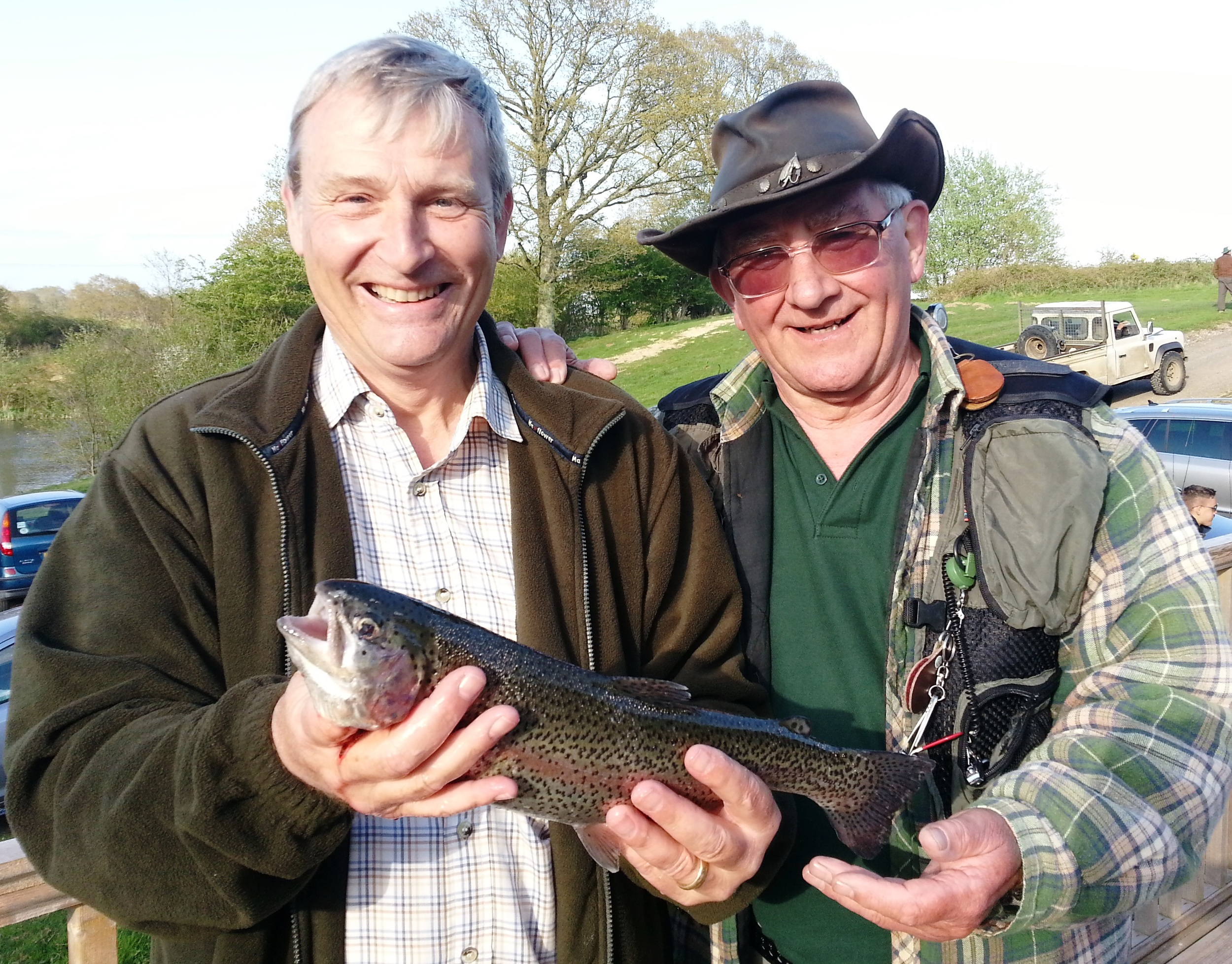 Paul Gietzen with his first ever fish helped by the experienced Fred Mitchell at Brick Farm's fly fishing taster evening
