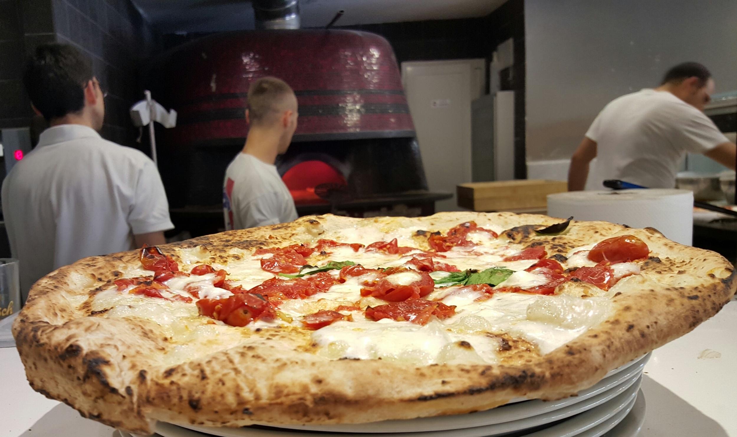 """Dietro la pizza """"Filetto fresco di pomodoro"""", Antonio e Nando controllano il forno a legna mentre Gennaro prepara un'altra pizza."""