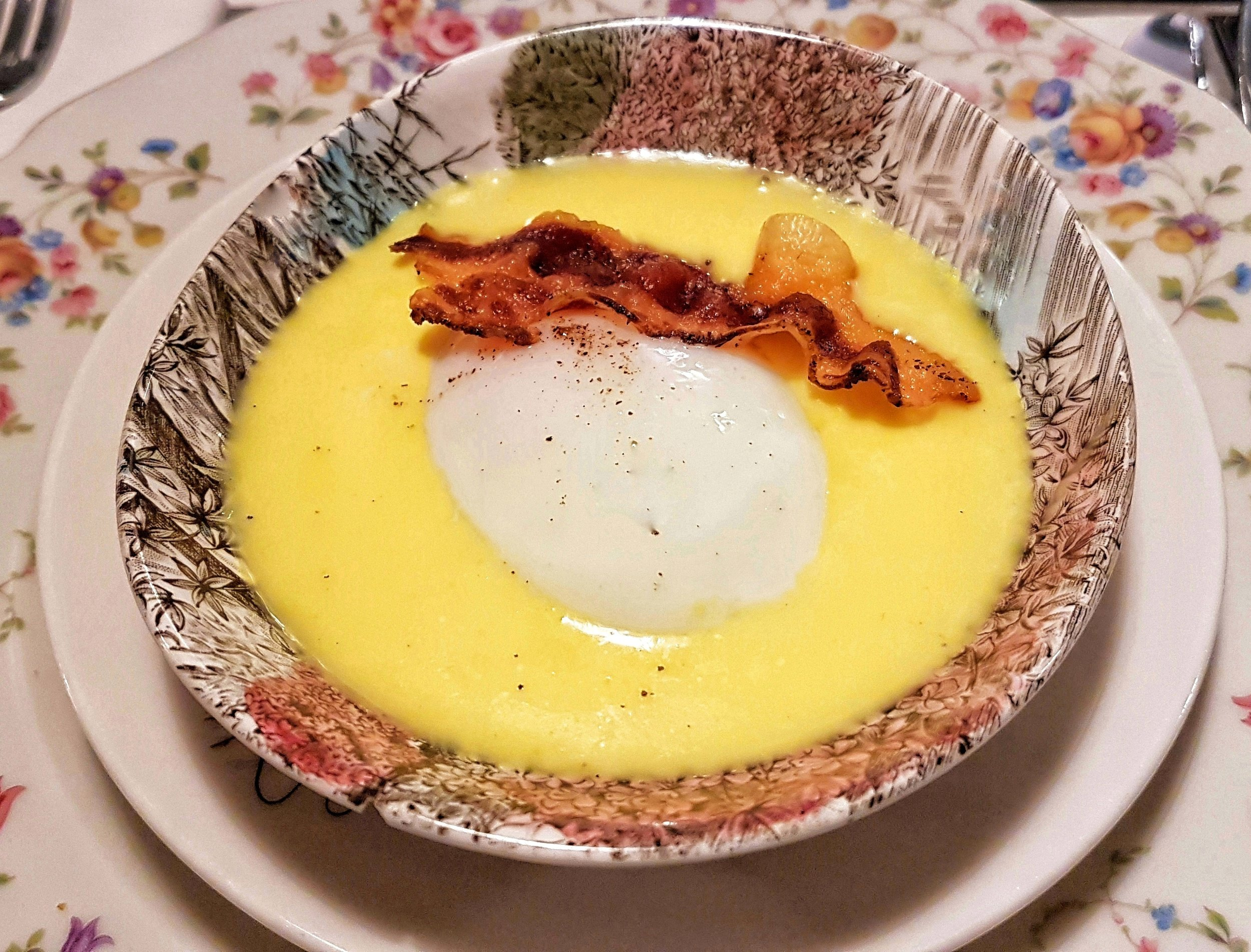 Poached egg in a sauce of risotto alla Milanese with crispy bacon