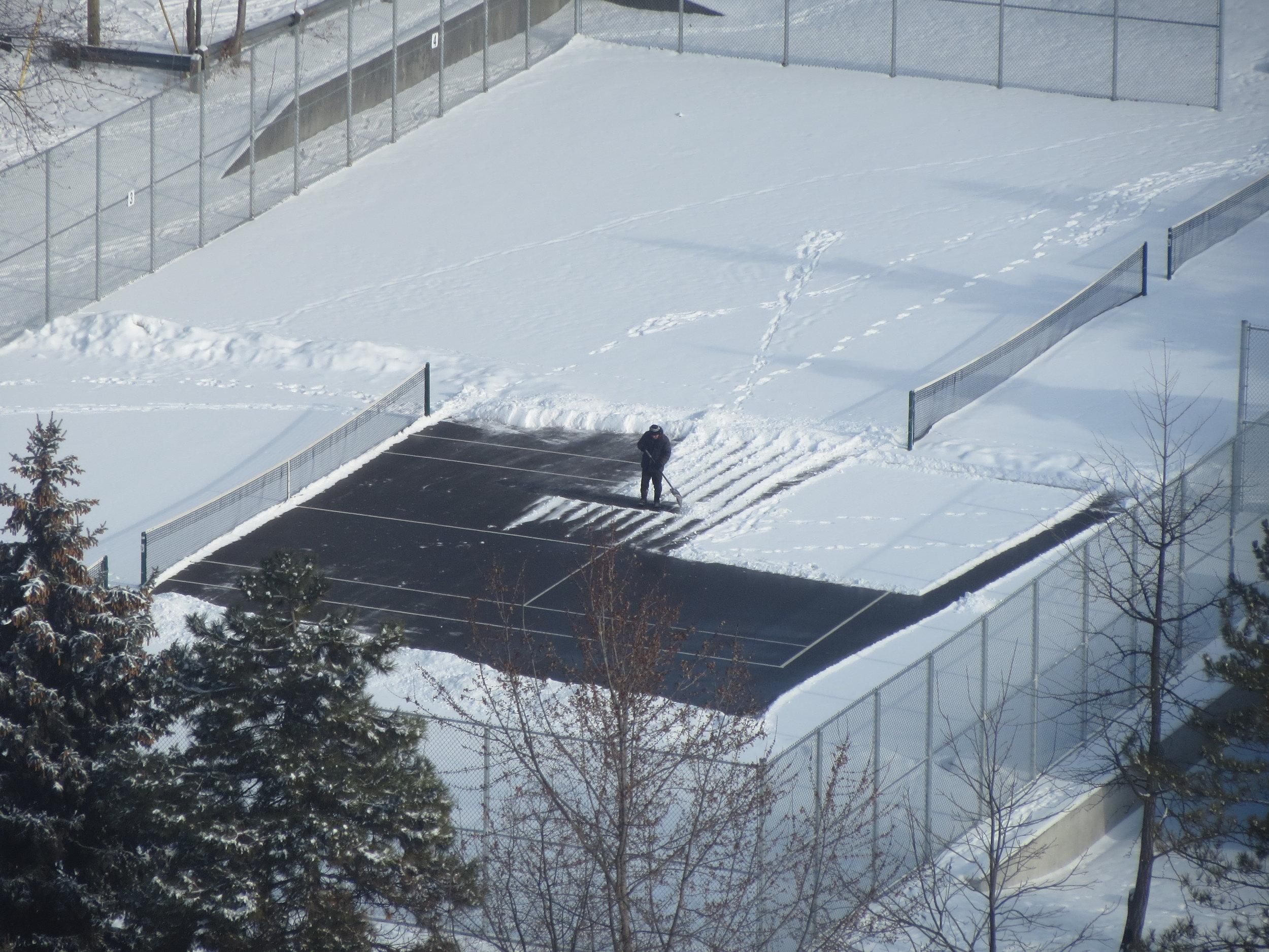 Shovelling the court.