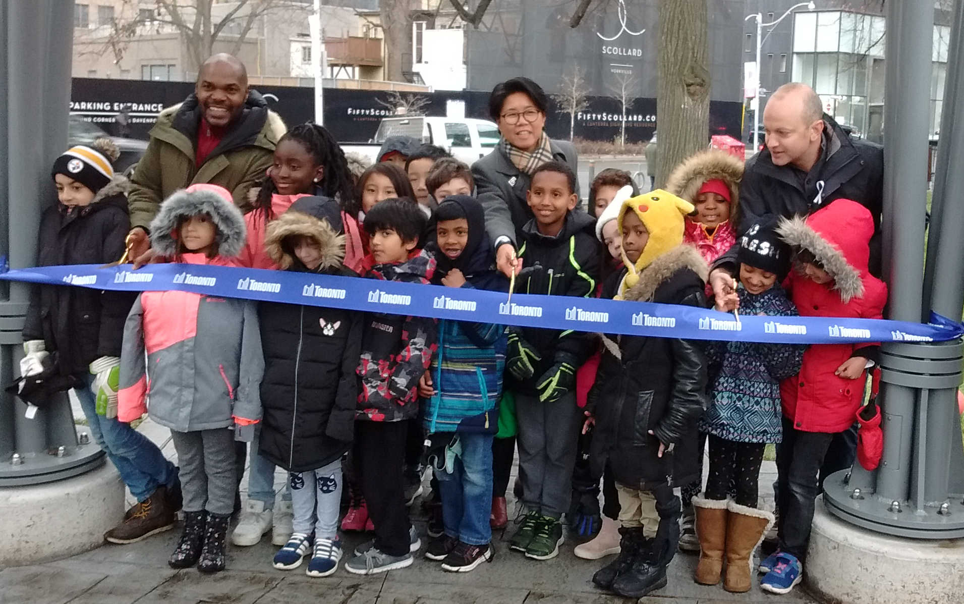 Chris Moise, Kristyn Wong-Tam, and Mike Layton cut the ribbon at the reopening of the Jesse Ketchum Parkette. They are joined by children from the Jesse Ketchum School.