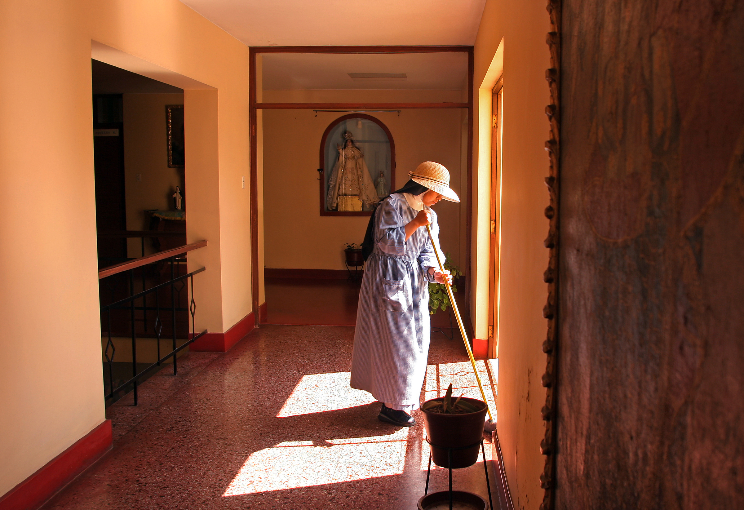 A nun mops the floor in the dormitory area of the monastery.