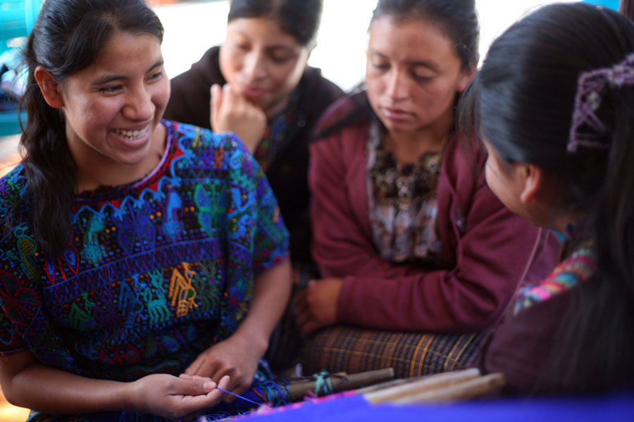 Claudia Nimacachi Lopez laughs with her friends while she weaves a huipil (traditional Mayan blouse) during a Starfish mentoring session. She said it will take her about a month to complete.