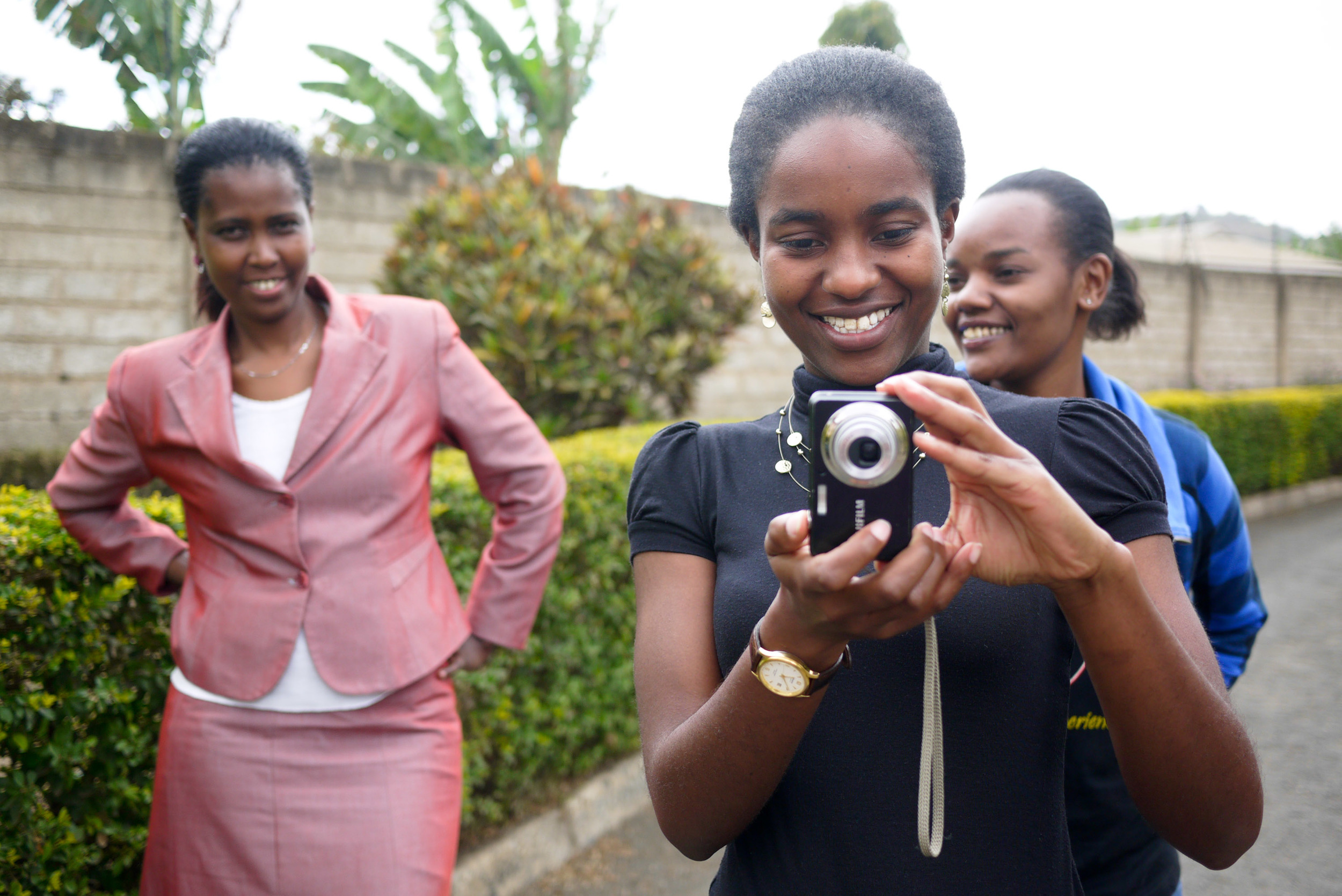 Anande, center, practices her new photography skills during a workshop.