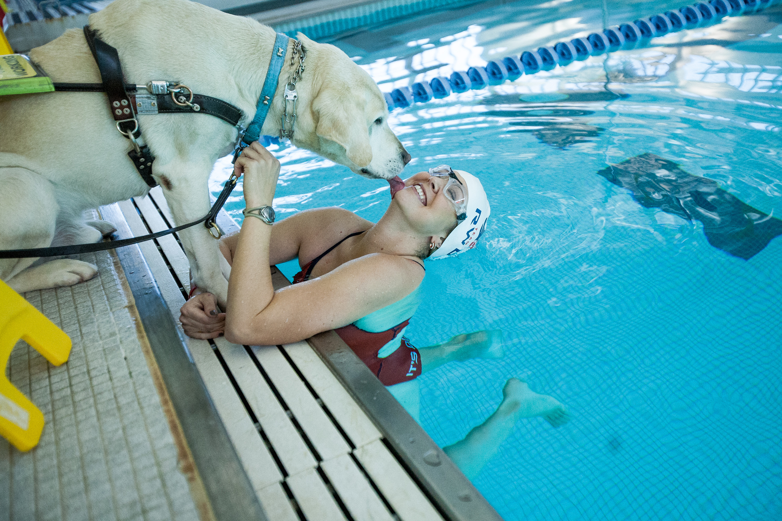 Amy Dixon, a visually impaired sommelier and triathlete, gets kisses from her guide dog Elvis at the YMCA at Greenwich in Greenwich, Connecticut, Thursday, Dec. 12, 2013. Dixon is training for several championship competitions next year, including the USA Paratriathlon National Championship and the PATCO Triathlon Pan American Championships.