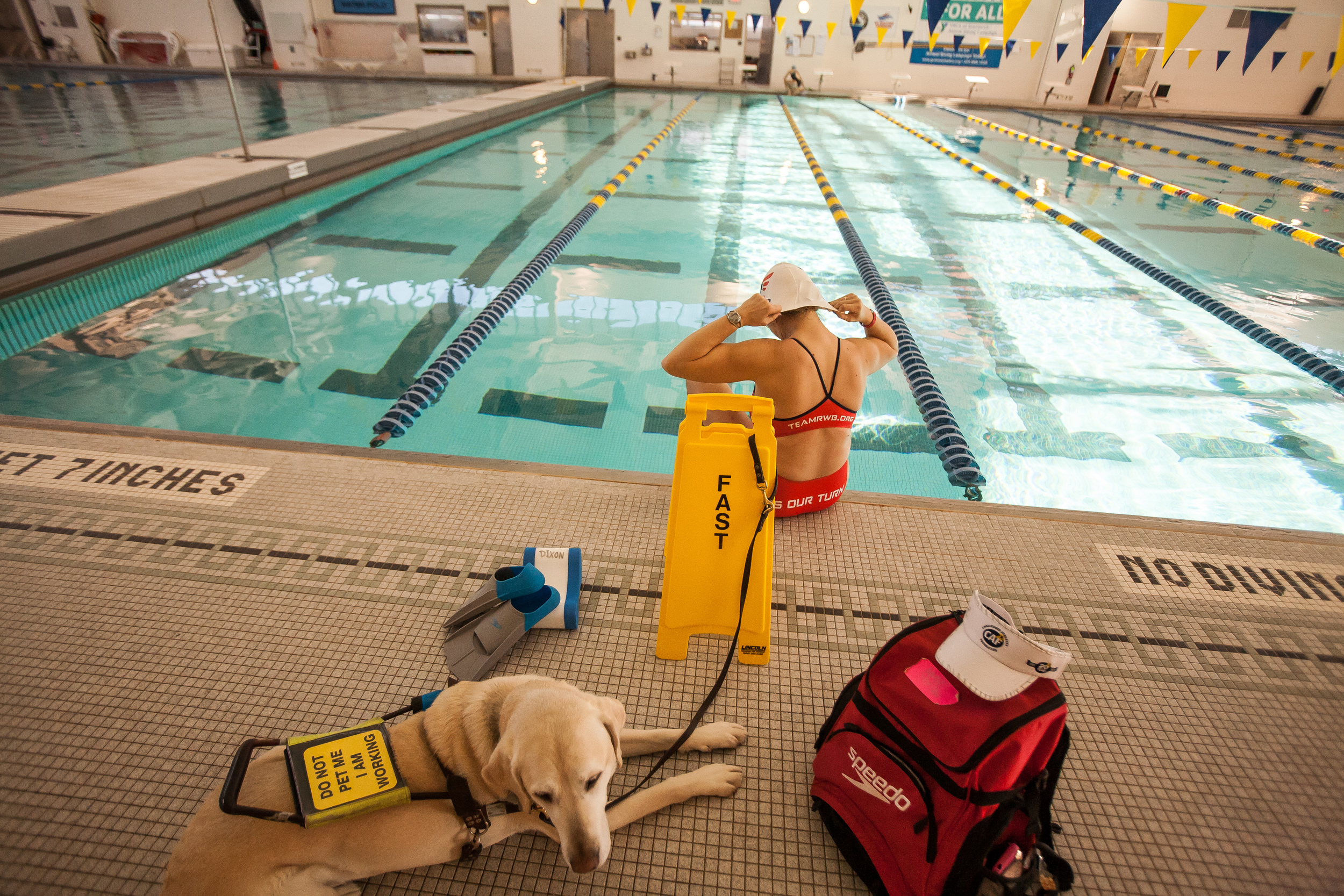 Amy Dixon, a visually impaired sommelier and triathlete, puts on her swim cap before a light swim workout at the YMCA at Greenwich in Greenwich, Connecticut, Thursday, Dec. 12, 2013. Her Guiding Eyes for the Blind guide dog Elvis stays close by.