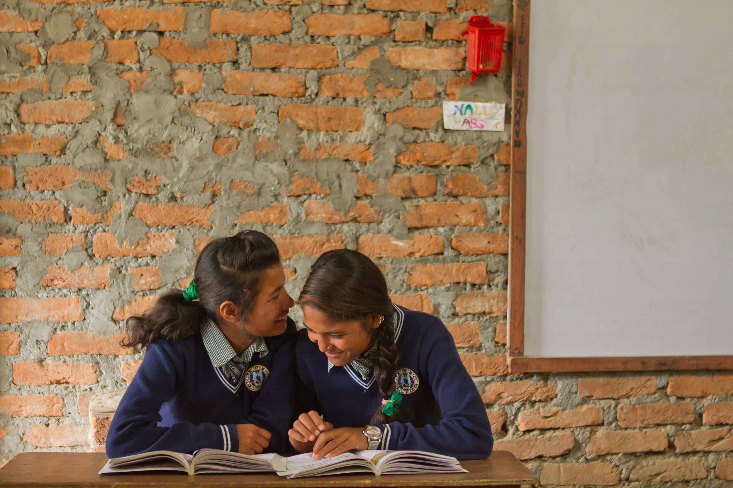 She's the First Scholars Kamala S. and Shanti S. whisper to one another at school in Nepal, March 2015. (photo by Kate Lord)