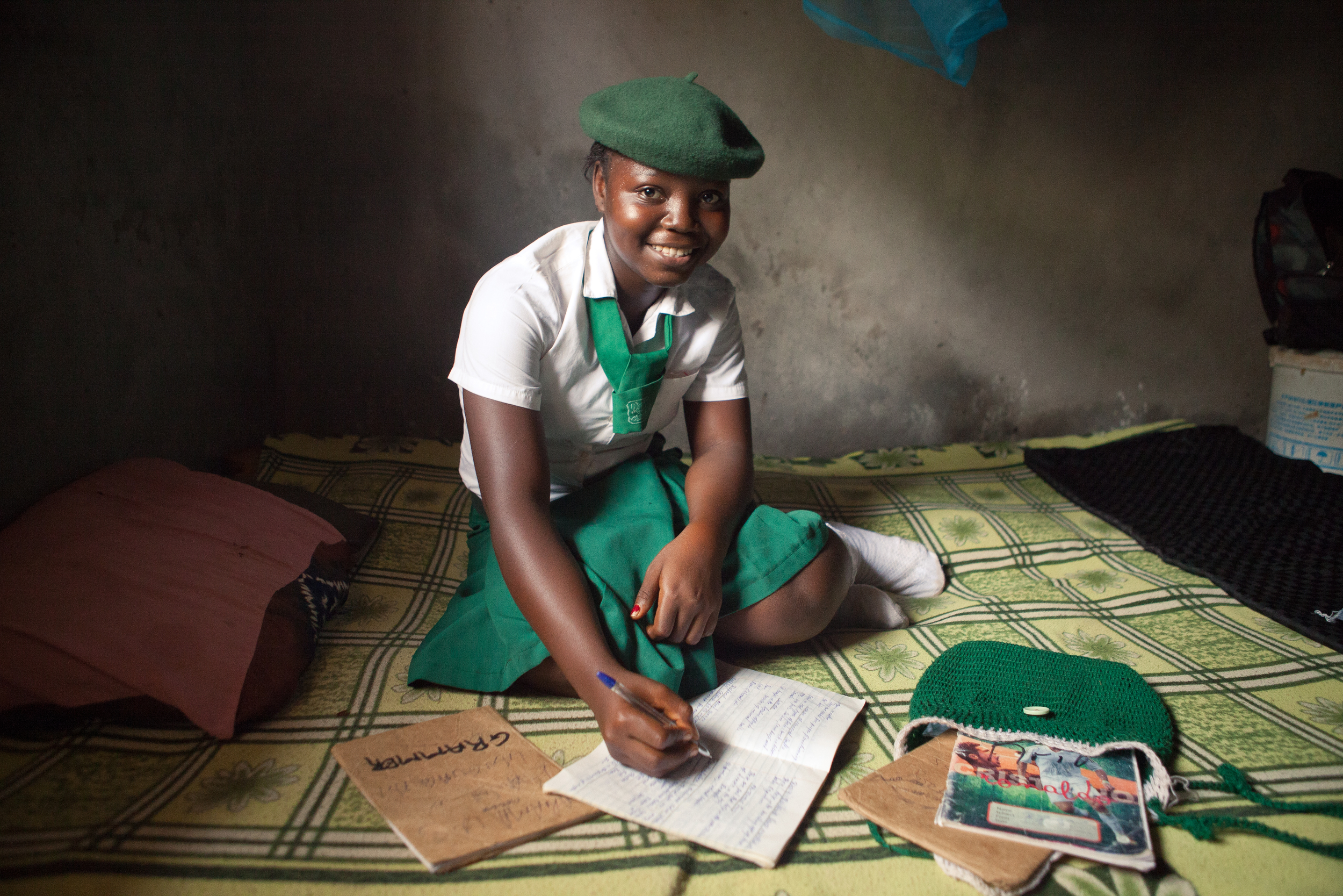 Mariama, 14, does homework in her room. She's the oldest sibling and helps her younger brother and sister with their schoolwork.