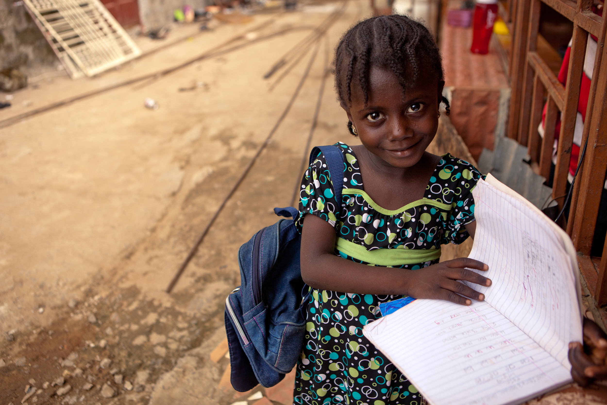 Seven-year-old Ismatu K. poses outside her home with her book bag. her older sister Mariama, also a She's the First Scholar, helps her with her homework everyday.