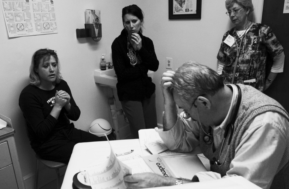 Dr. Stover scratches his head as he listens to new patient Laura, left, describe her daily regiment o keep her diabetes in check. Nurse Practitioner Blessing, center, is learning the ropes to become a volunteer provider so that the clinic can open an additional night during the month. Nurse Lipinski, right, waits for the doctor's instructions on how to proceed with Laura's prescriptions.