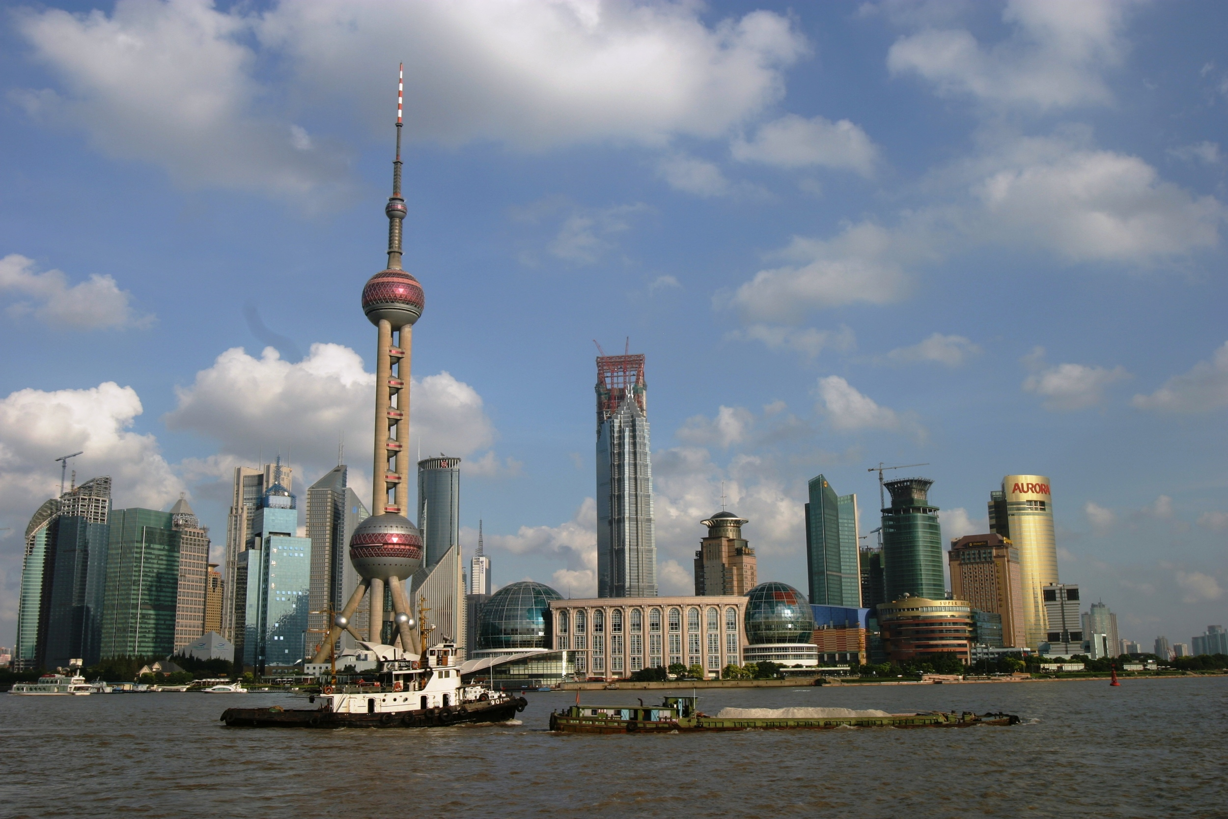 Boats float down the Huangpu River in downtown Shanghai, China overlooking the city's Pudong district. The Oriental Pearl TV Tower rises above the rest of Shanghai's skyline.