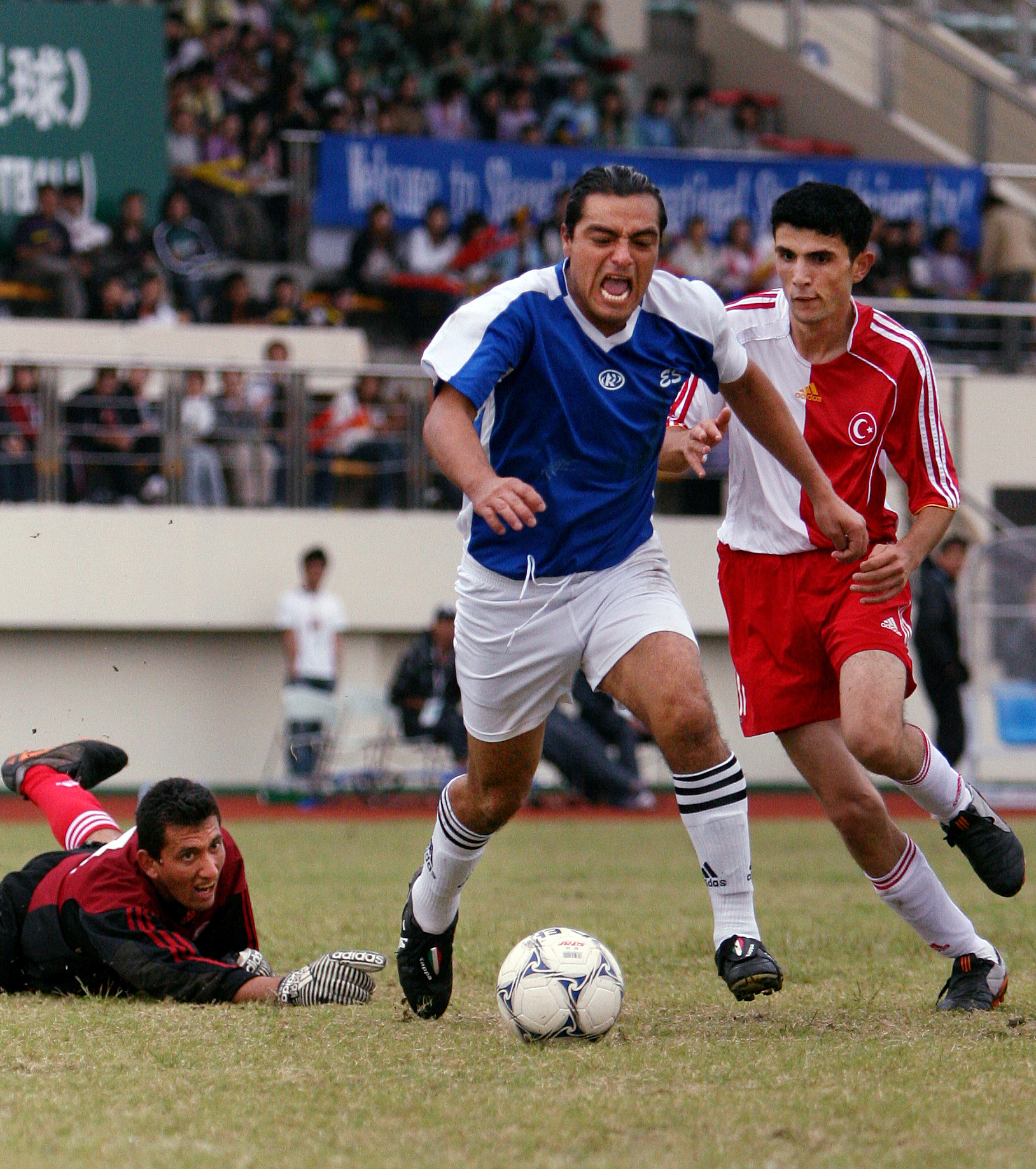 Gustavo Deras of El Salvador rushes past Turkey's Ismail Sari and Ozgur and Ozgur Tas in a match-up during the 2007 Special Olympic World Summer Games at Shanghai International Studies University Stadium.  El Salvador won the match.