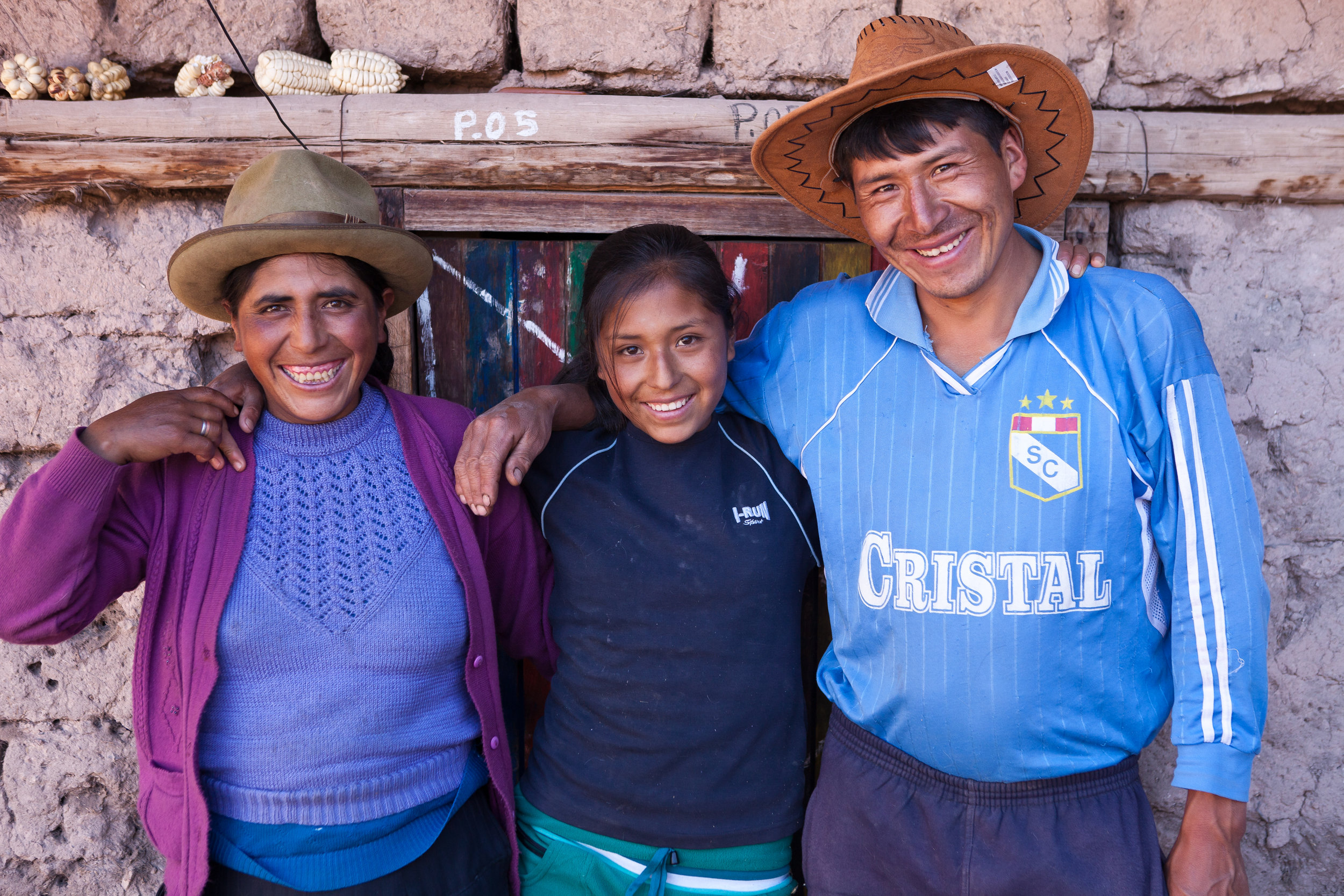 Mariela poses with her parents outside their home. She lives more than a five hour walk from the closest secondary school; without Sacred Valley Project's dormitory, she would not be able to attend.
