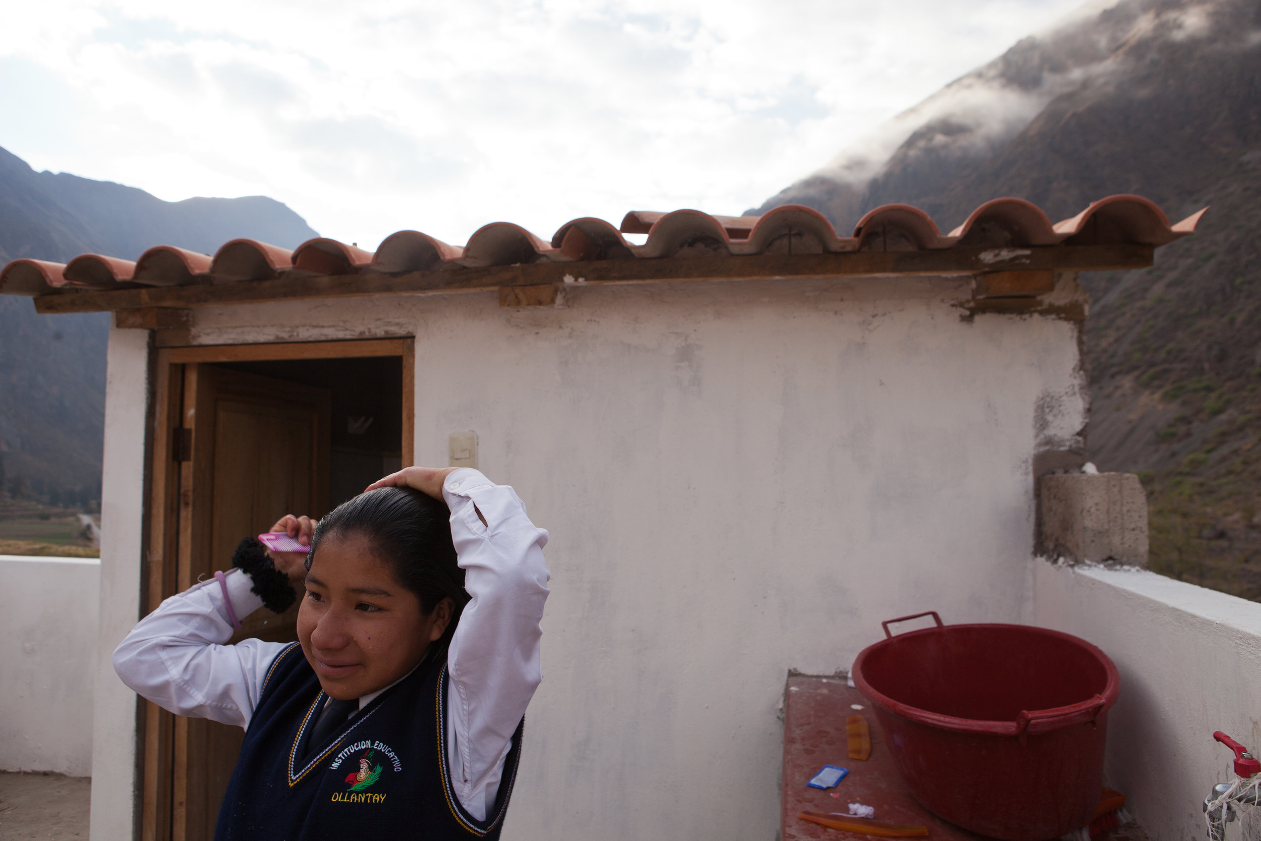 5:30am: Elizabeth wakes up and starts her day. Here, she combs her hair outside the dormitory's upstairs bathroom. The fifteen girls manage to split two bathrooms among all of them! All of the girls' basic needs are supplied by the Sacred Valley Project, from their housing to their uniforms.