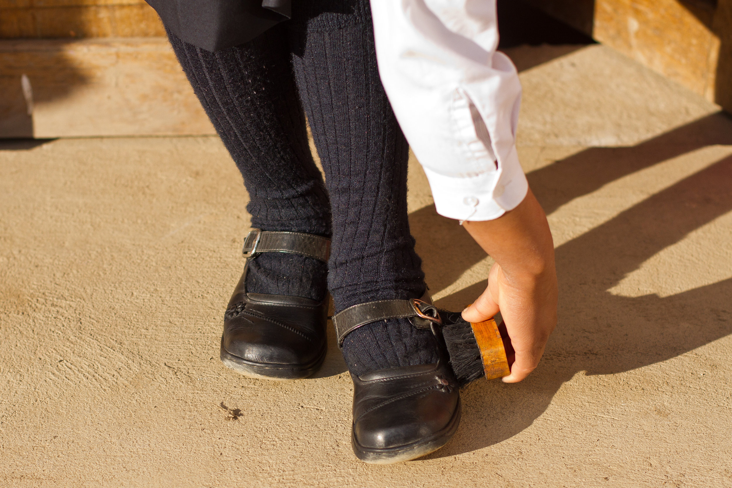 A She's the First Scholar polishes her shoes before heading off to school.