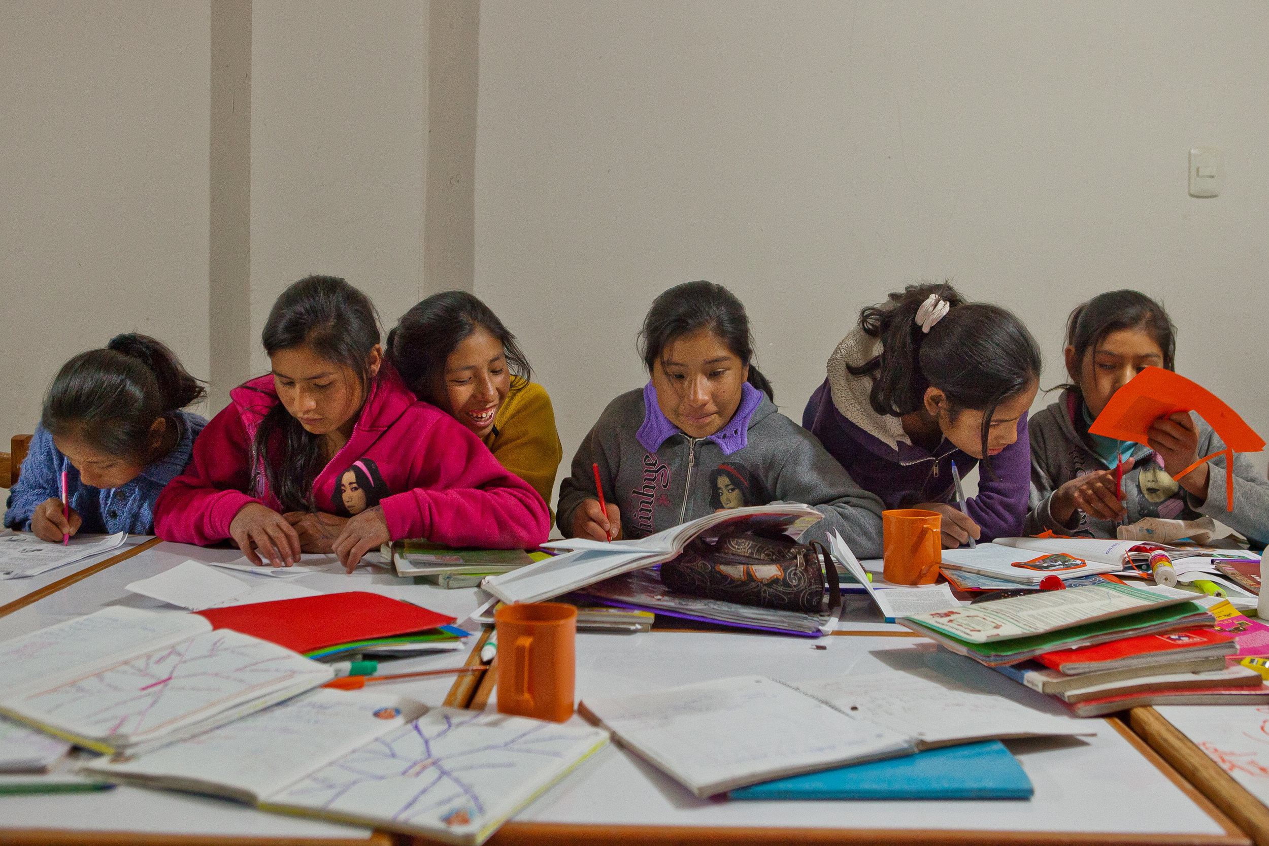 After school each day, the girls gather to work on their homework together. From left, Mariela, Marisol, Nilda, Elizabeth, Nayda, and Flor Nayda work on various homework assignments.