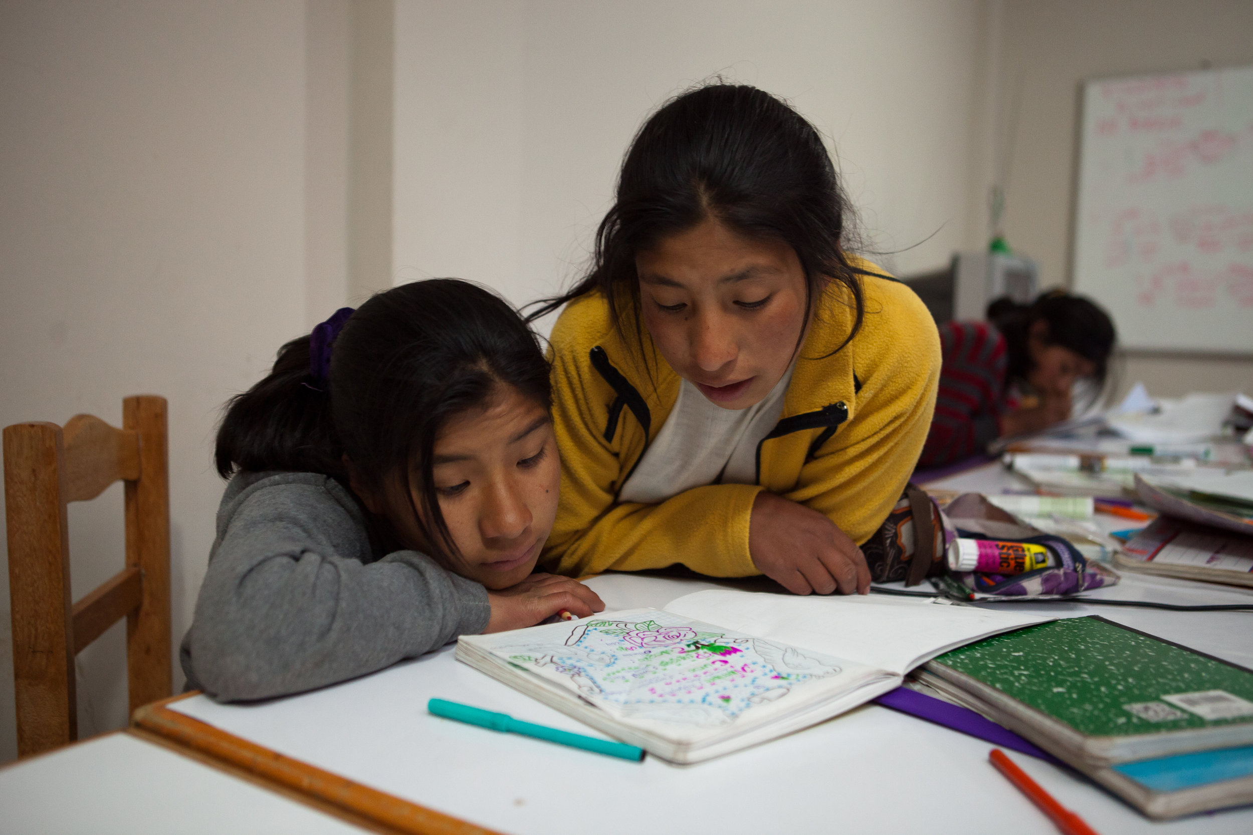 Elizabeth and Nilda look over notes from the day's classes during homework time. 15 girls live in the dorm together and are all in secondary school - the older girls often help the younger girls with their studies.