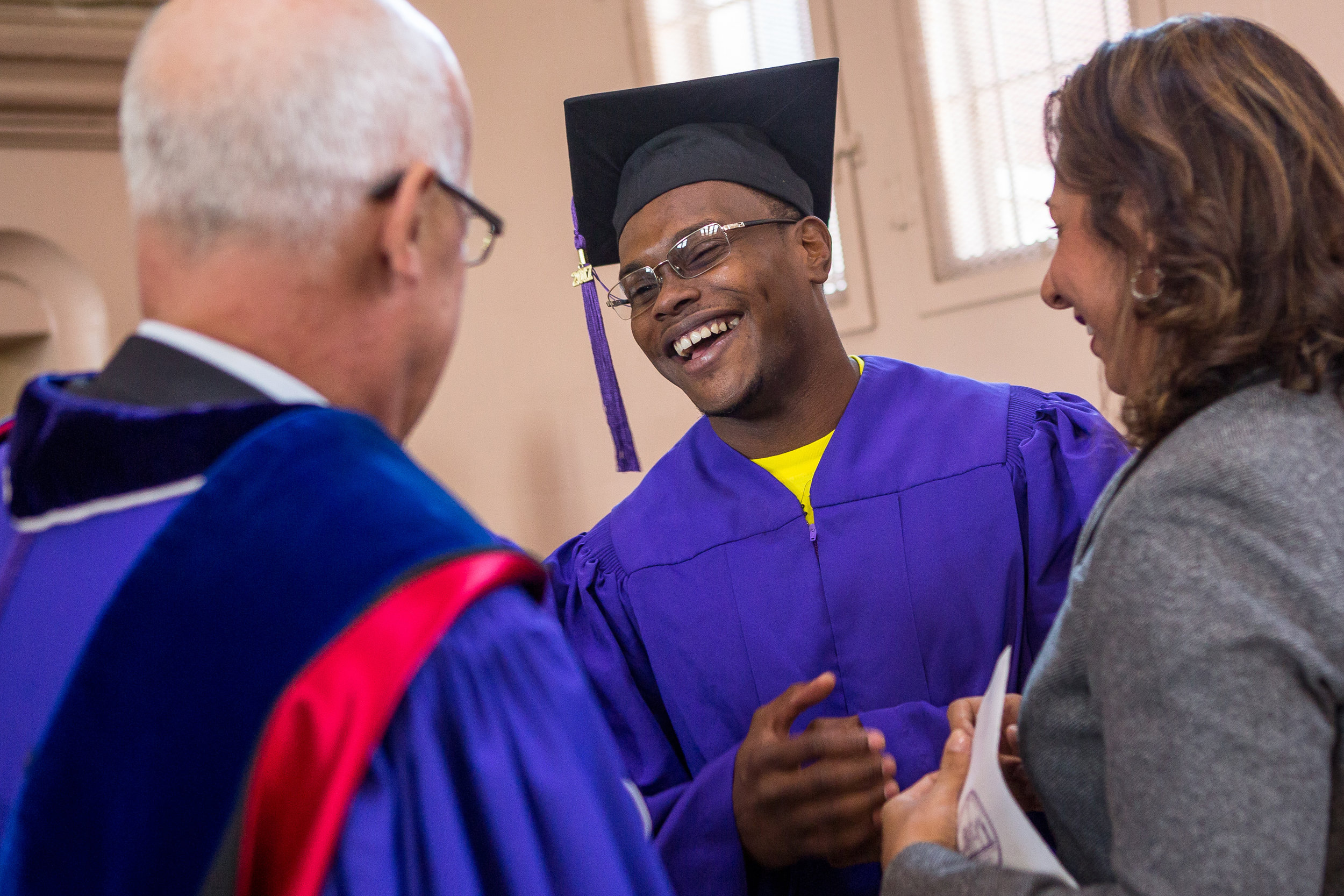 Graduate Roy Burvick chats with NYU President Andrew Hamilton. This is the first graduation for NYU's Prison Education Program.