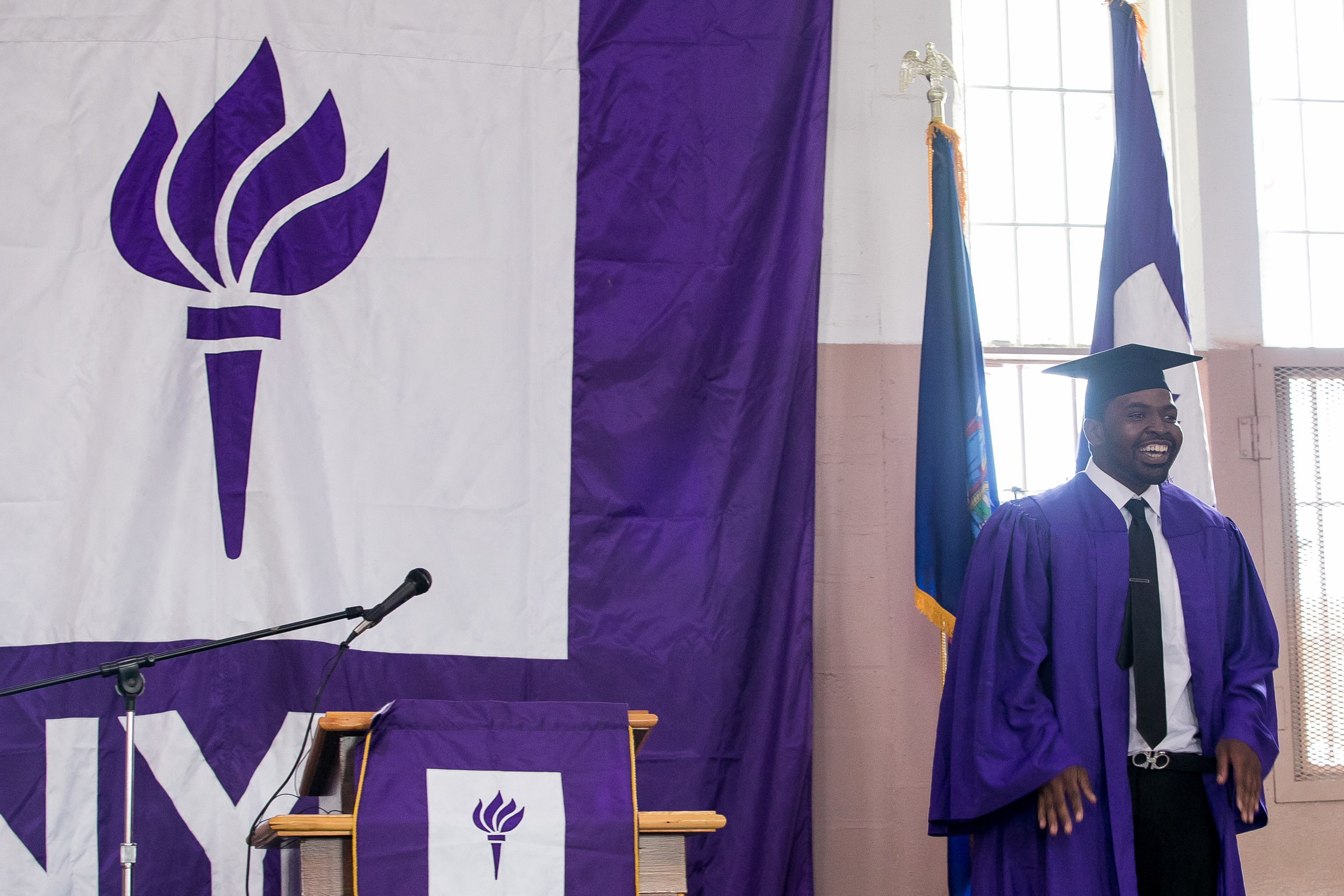 Vincent shows off his suit under his graduation gown. He has been released from Wallkill but came back for graduation, which he said was difficult, but he was glad that he did. He's working with program staff to continue his education at NYU's main campus.
