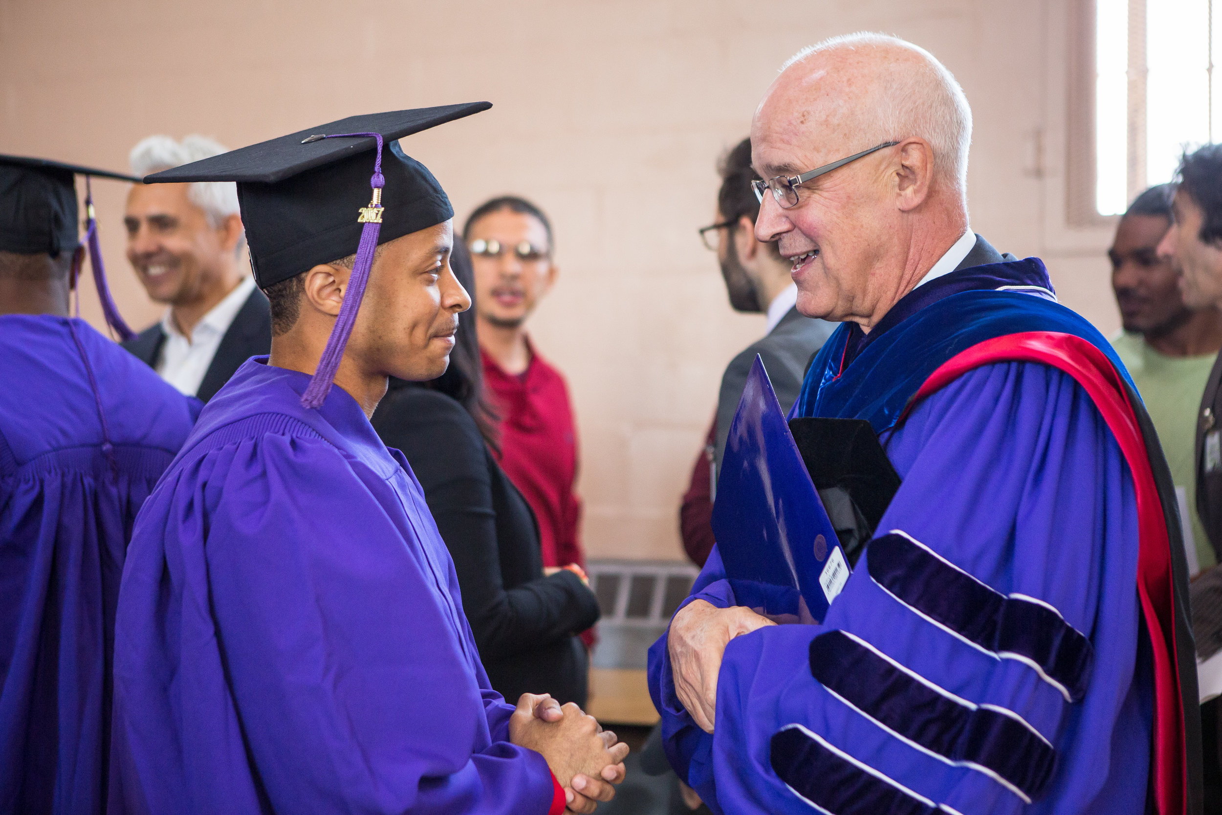 Graduate Khalan Pendelton meets NYU President Andrew Hamilton. The program offers credit-bearing courses and educational programming.
