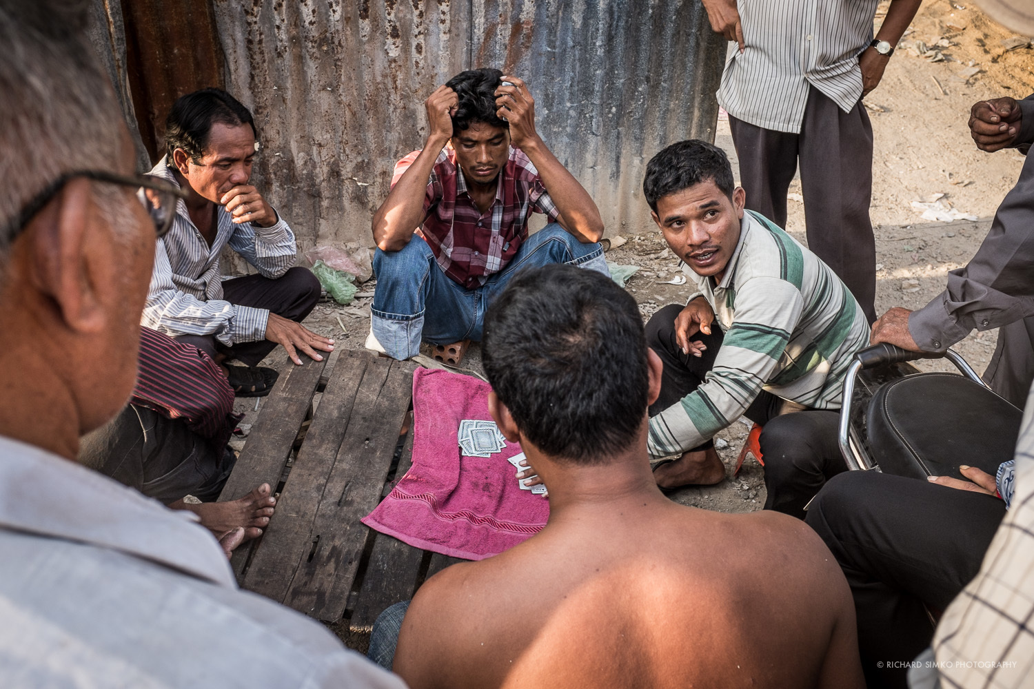 Men playing cards in late afternoon heat. Kandal market, Phnom Penh.