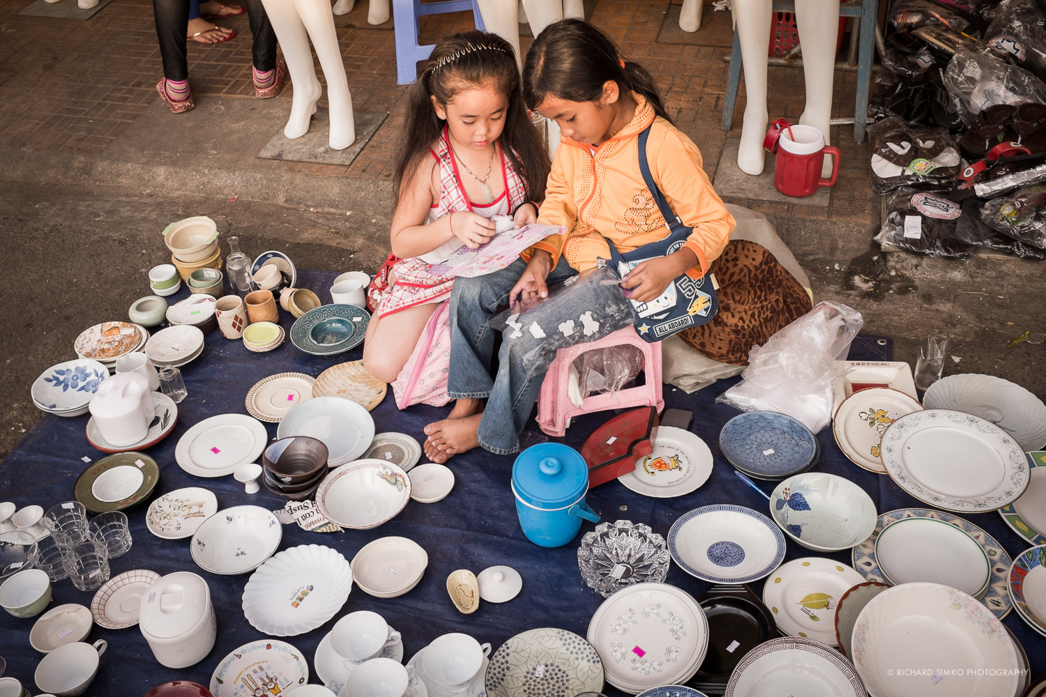 """Girls discussing """"girl stuff"""" in the middle of pottery stall."""