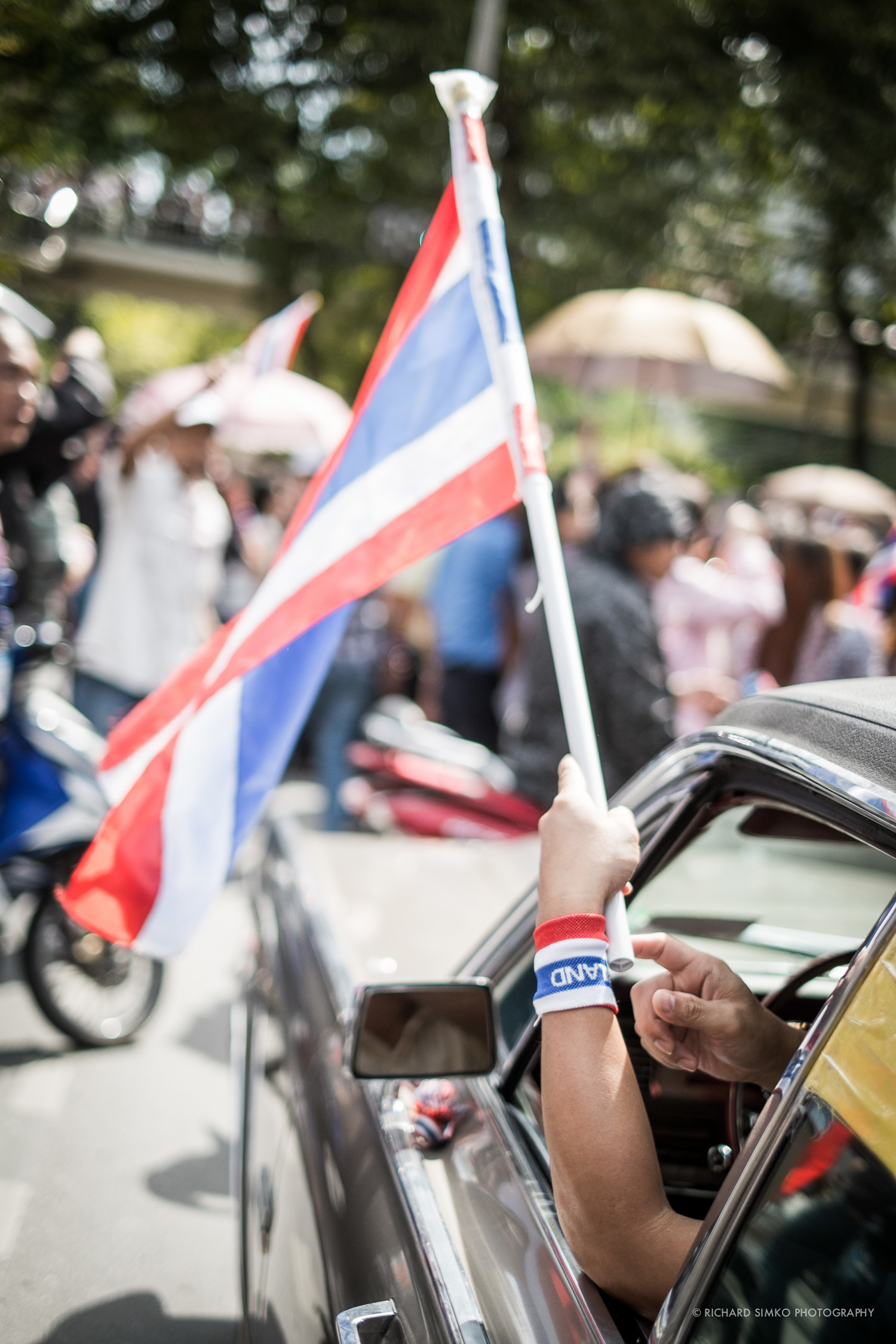 Protester is waving thai flag from the window of his car in front of US Embassy.