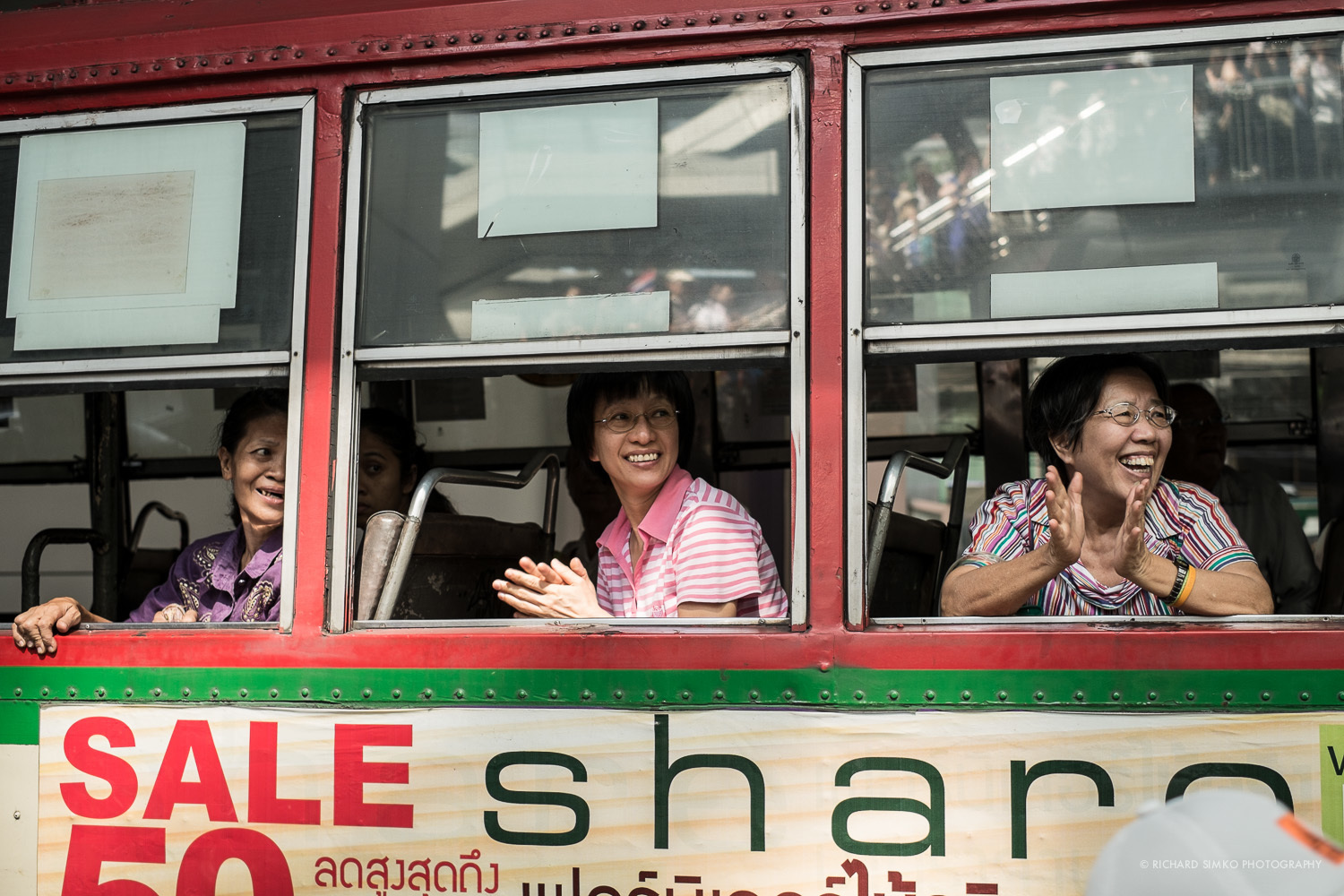 Bus passenger watch the protesters and cheering while bus got caught in gridlocked traffic in Asok.
