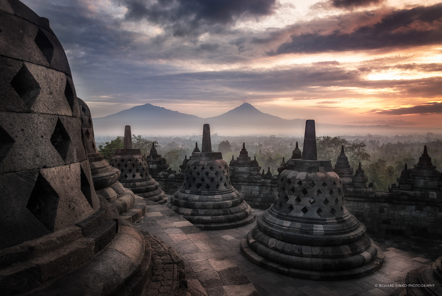 Sunrise at Borobudur temple with Merapi and Merbabu active volcanoes in the distance