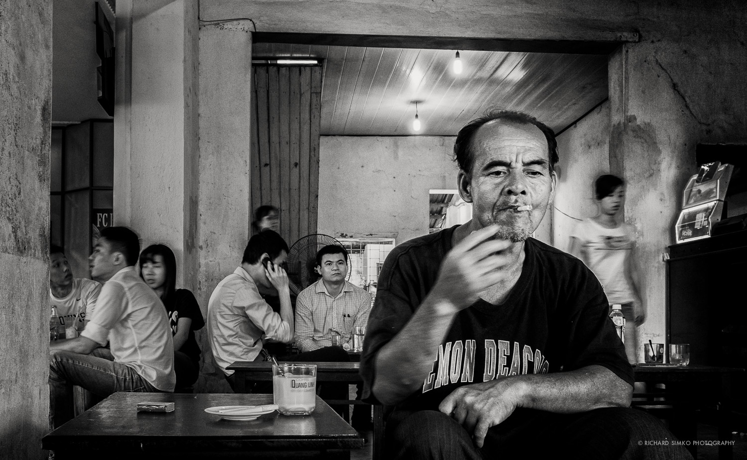 "This photograph was taken in one traditional Vietnamese coffee house located near Da Nang's riverside. I was enjoying my (very tasty) coffee when this man came in and sat down right behind me. I looked around and observed him for a while. As I was the only ""white dude"" there I waited till he gets used to my presence.  I had my Fuji X100s with me at the time and I pointed the camera towards his direction without turning. I snapped few pictures and this one came out best right in the moment when he is sucking the smoke into his lungs."