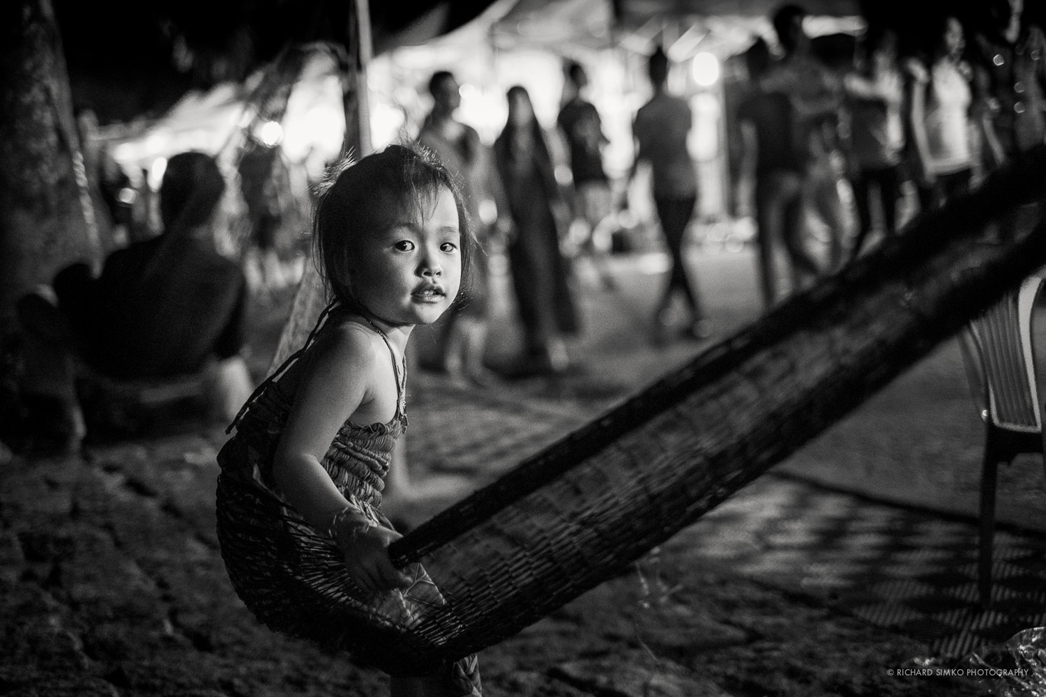 Hue, the ancient capital of Vietnam has a beautiful riverside with a night market that offers tons of photographic opportunities. I came across this little girl sitting on hammock. She was initially looking ahead and I wanted to capture a detail of her hand holding onto hammock. I got very close to her and took about 4-5 shots when she noticed me and turned her head towards me. In that moment I quickly recomposed the shot and took this photograph.