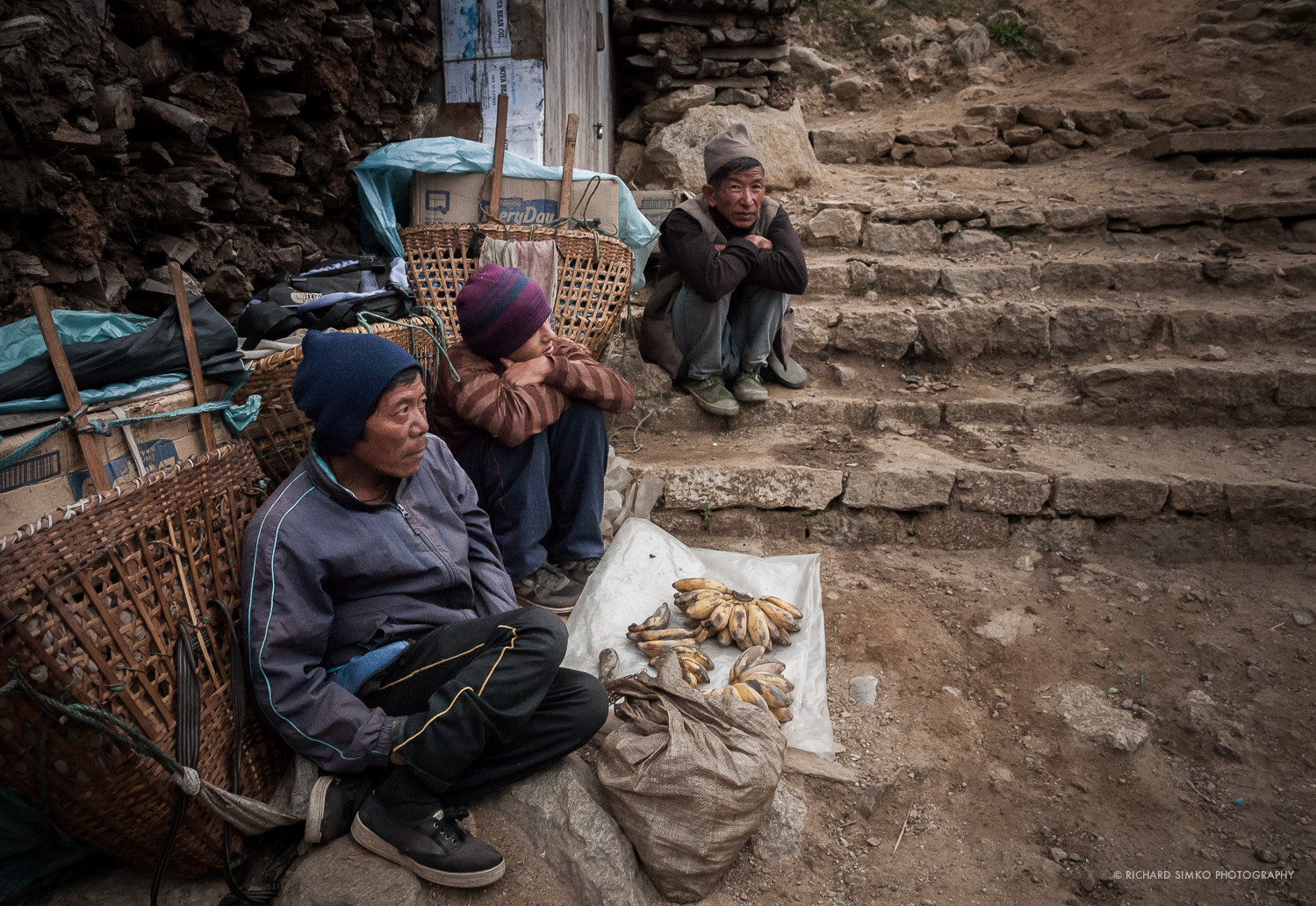 """Outskirts of Namche Bazaar market. Few porters trying to sell lst remaining goods before heading of to their home village. Namche Bazaar is the biggest village in Everest Khumbu region and is comonly refered to as """"Sherpa Capital"""". It is located at  3,750 m altitude and serves as resting and acclimatisation place for trekkers and climbers to Everest region."""