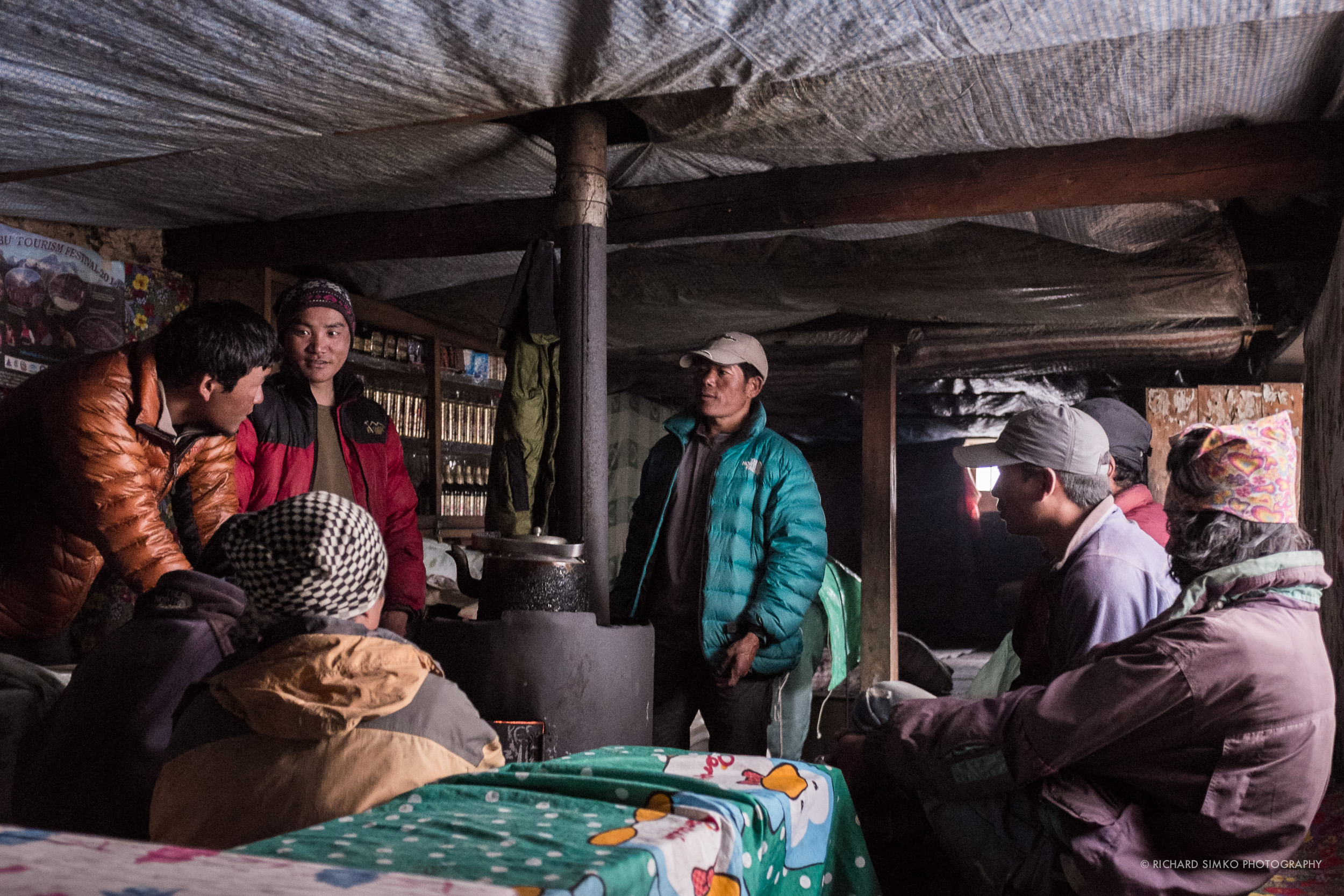 Sherpas gathered around fire place talking and warming up during the cold evening.