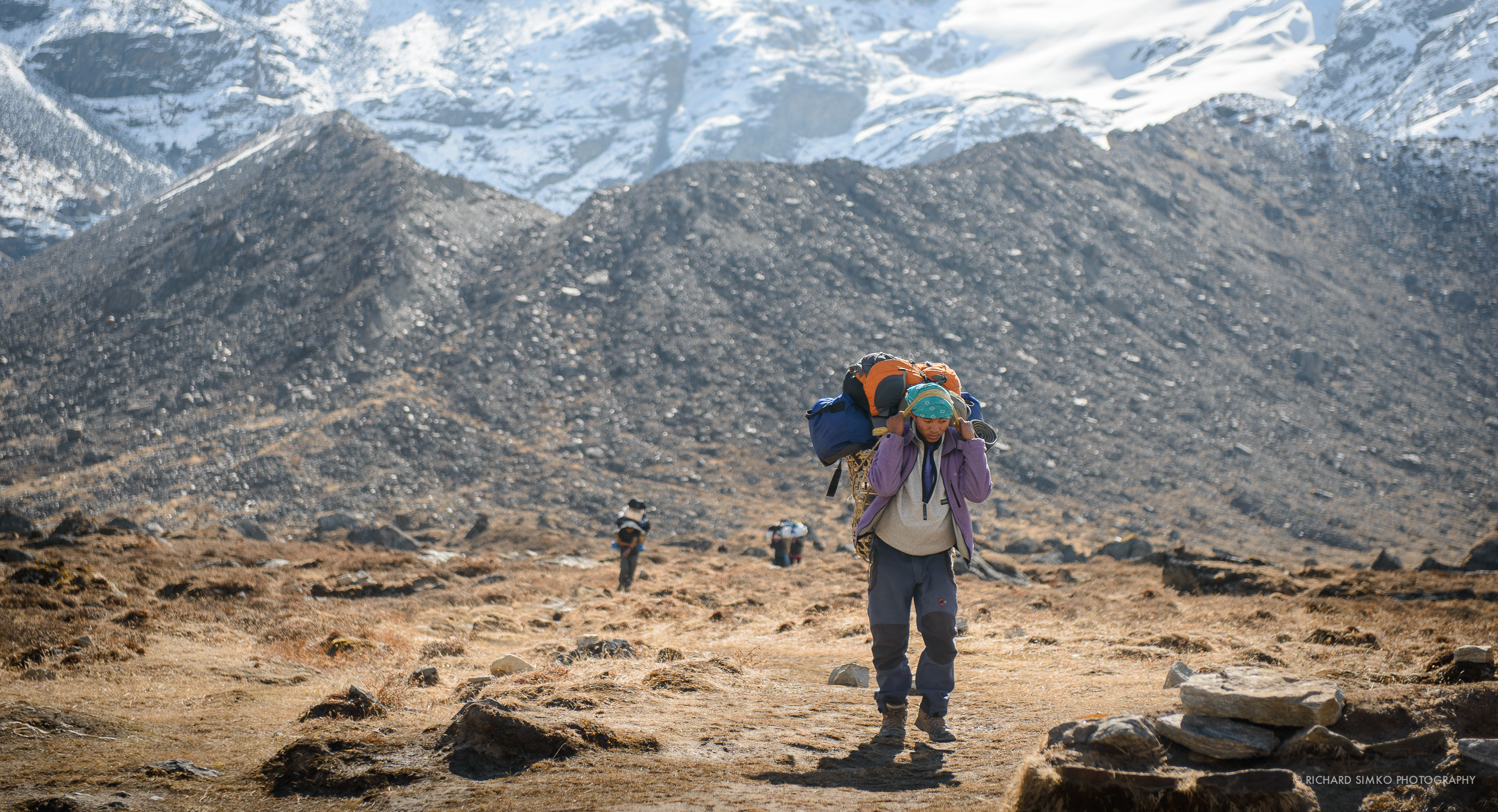 Sherpa carrying a backpack on the way from Khare.