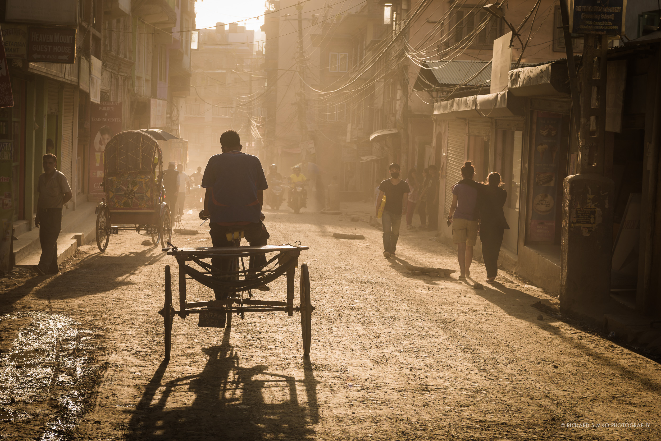 Late afternoon dust creates golden monochromatic glow in one of the dustiest streets in Kathmandu's Thamel district.