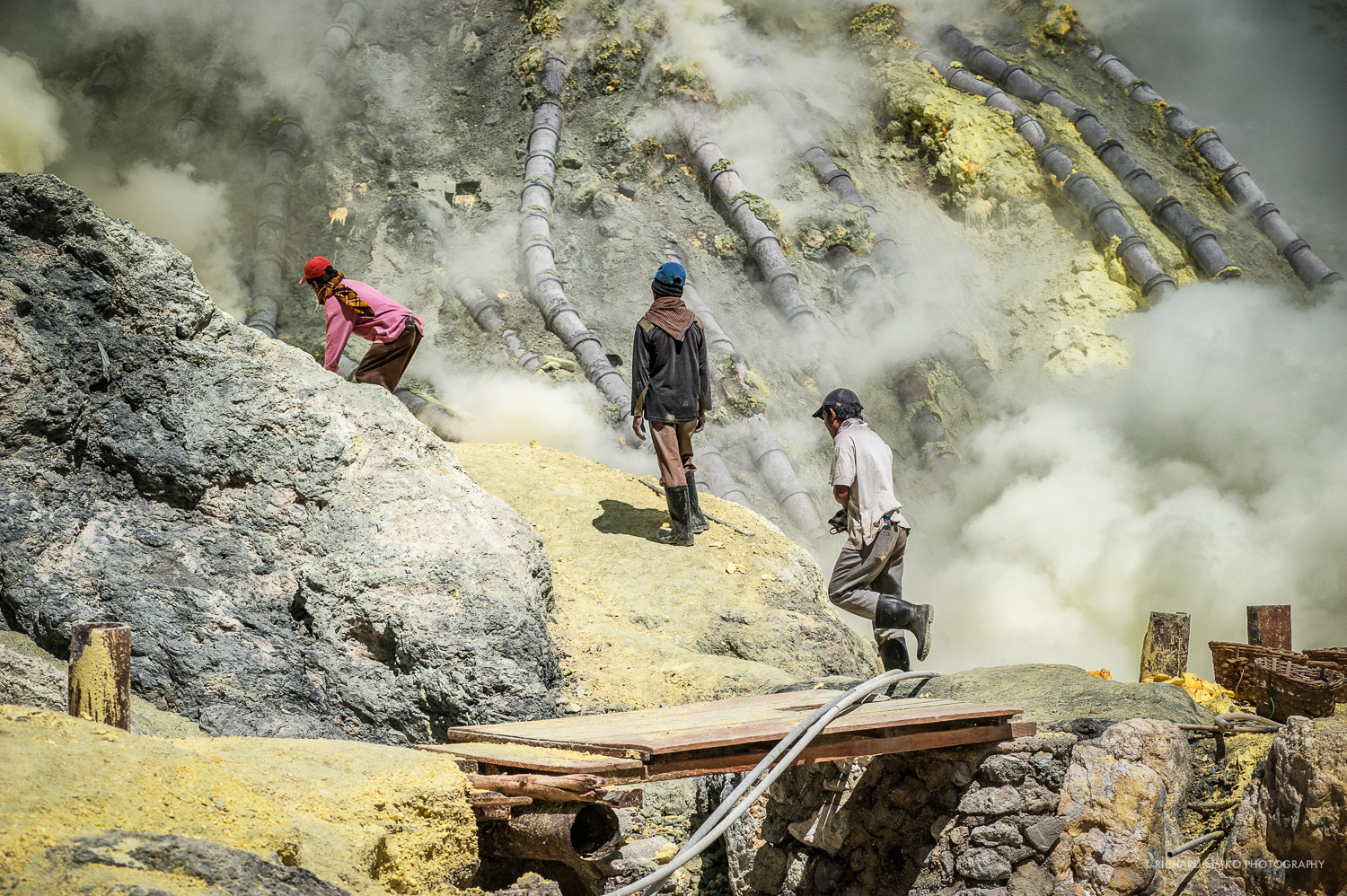 Ordinary day in the crater of Kawah Ijen.. Miners are turning molten sulfur into a rock which is then loaded into baskets and carried out of the crater. This is very unhealthy place for work. Of course they don't have mask protection and air is filled with fairly dangerous sulfur gas. There is not too much room to escape it so if the wind blows your way, it is your bad luck.