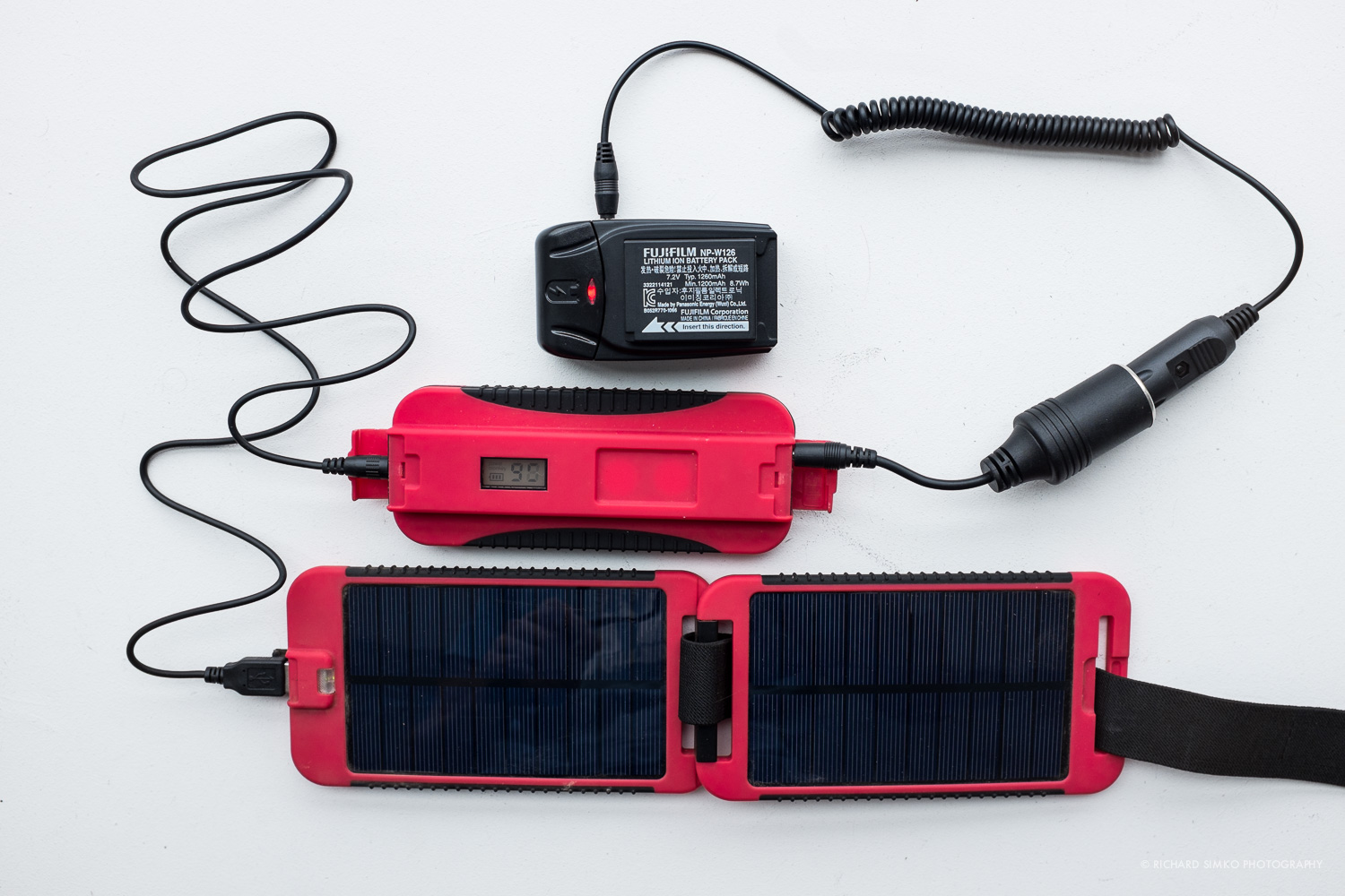 "Camera battery charging on the go. Solar panel is charging the 12V output battery which is connected to Watson charger via DC connector. In cloudy days or during the night I can use ""battery only"" charging."