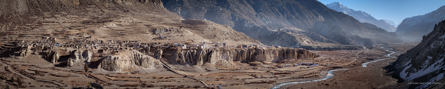 This is extremely wide panoramic photo of Manang village in Nepal. It is stitched together from 11 images. This is an example where image could be improved by shooting one or two more rows.