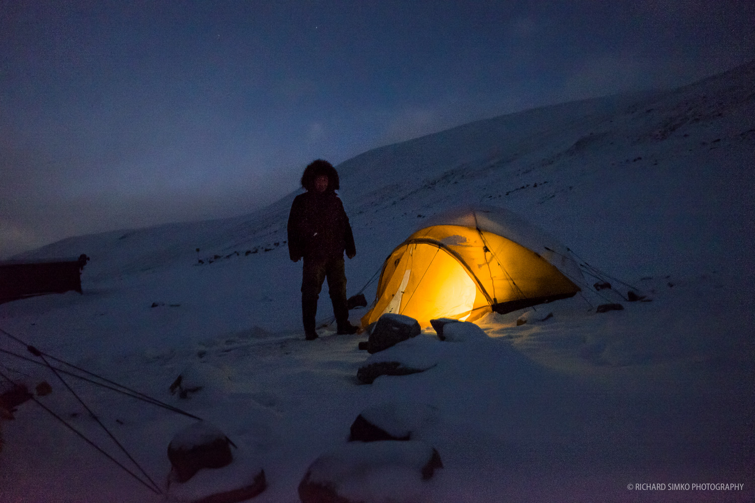 Freezing night at basecamp. It is almost pitch black only headlamp inside the tent is illuminating the immediate surroundings.