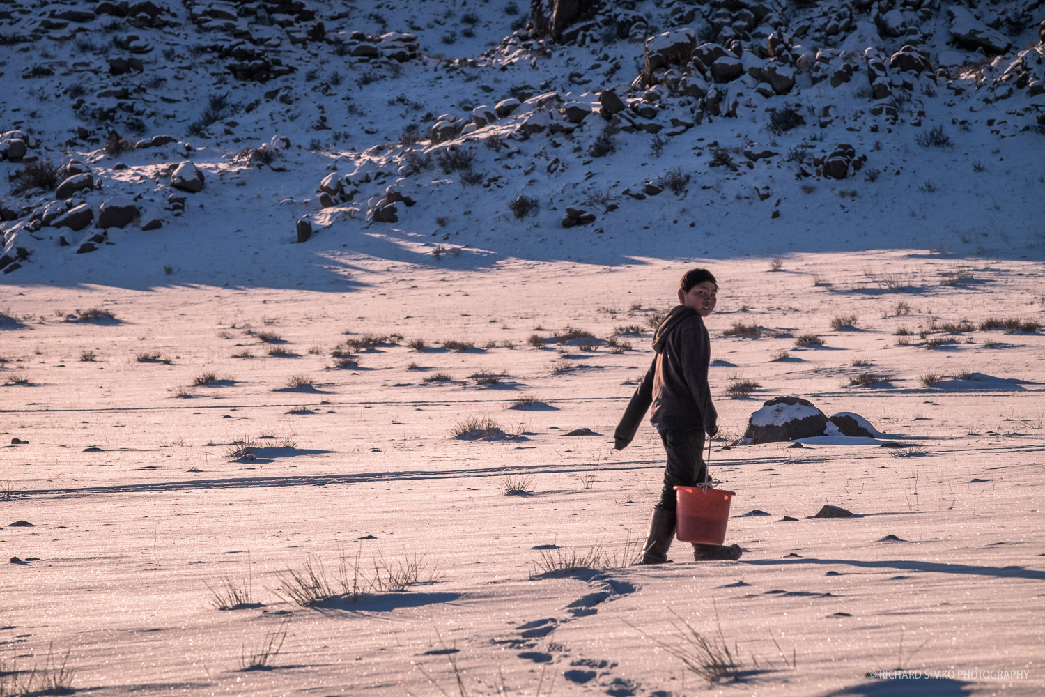 Boy from neighbouring family is taking out waste to a specific place away from ger.