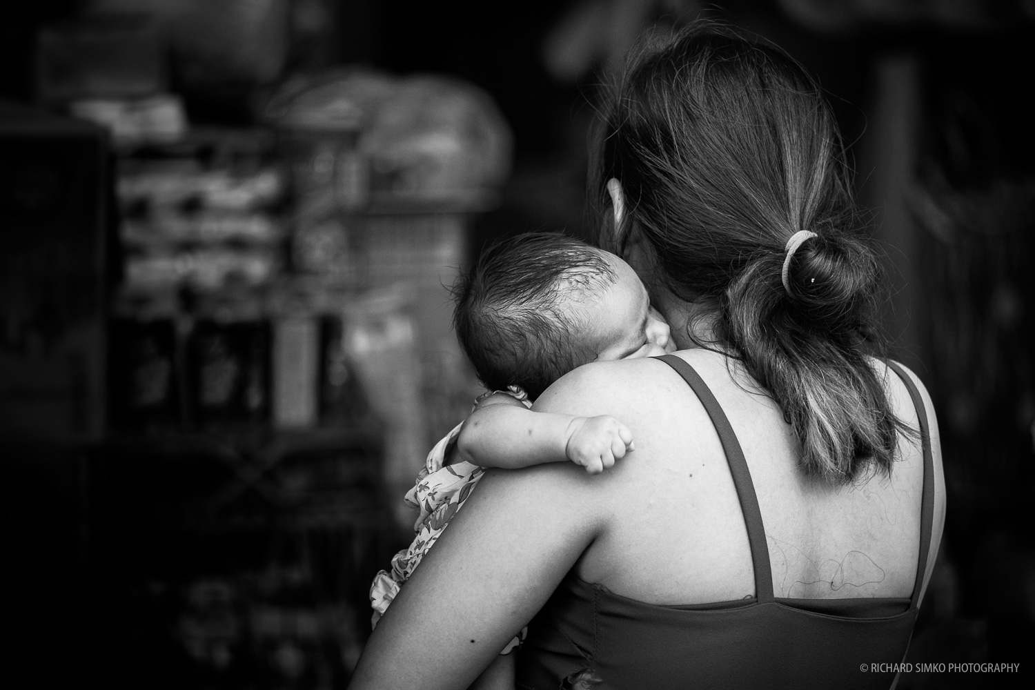 Woman stepping into the shop with baby sleeping on her shoulder. Photographed in Kandal market area in Phnom Penh. Fujifilm X-T1, Fujinon 50-140mm  2.8