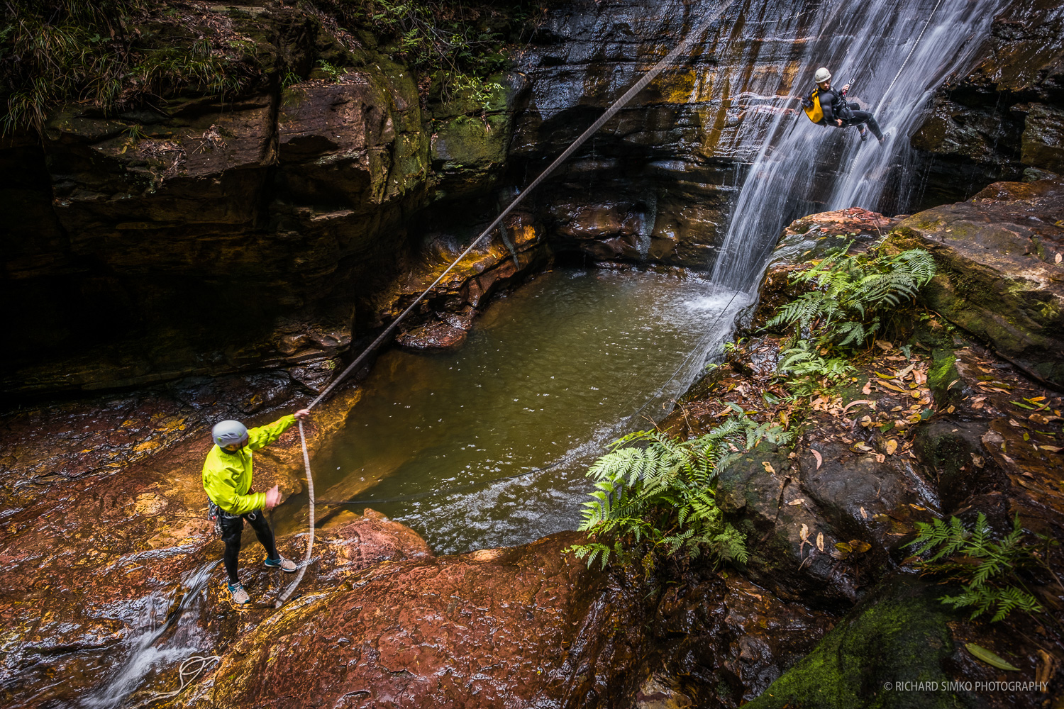 Canyoning instructor is belaying a client at Wentworth Falls.