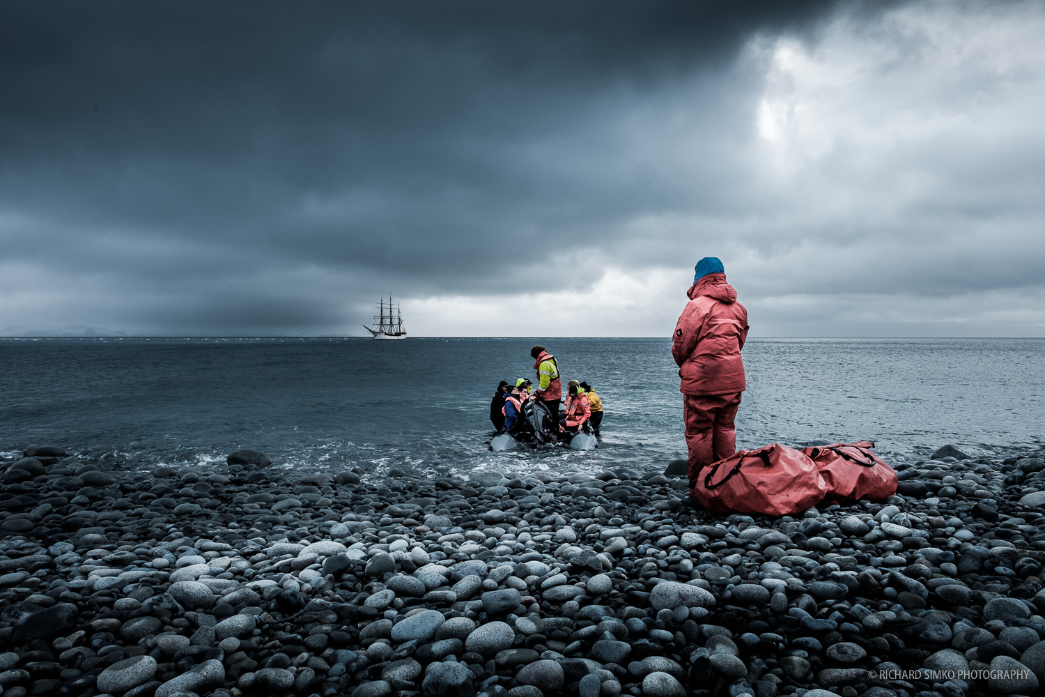 Europa anchoring at the shores of Deception Island. The crew on the zodiac is landing on the shores of Whalers Bay